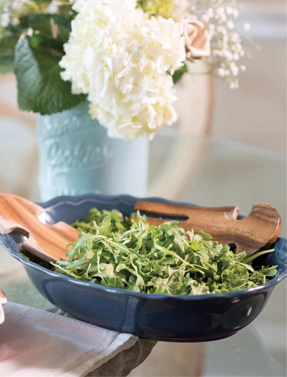 Arugula gets tossed with a bright dressing composed of spring onions, olive oil, mustard, white wine, champagne vinegar, garlic, and capers.