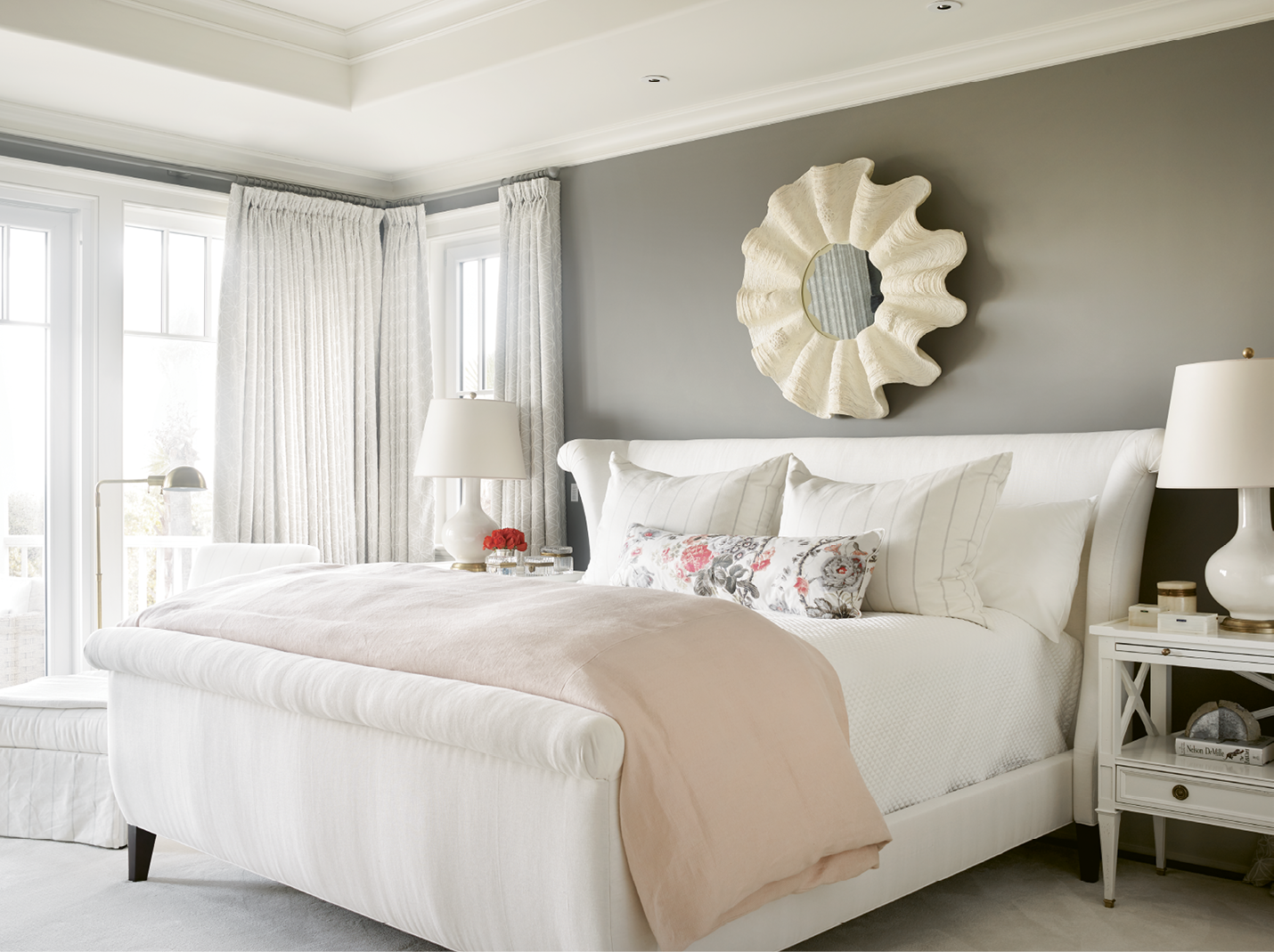 """In the master bedroom, walls covered in Farrow and Ball's """"Mole's Breath"""" and drapes made with light grey Shumacher fabric ground the room's blush accents. The lamps are from Circa Lighting."""