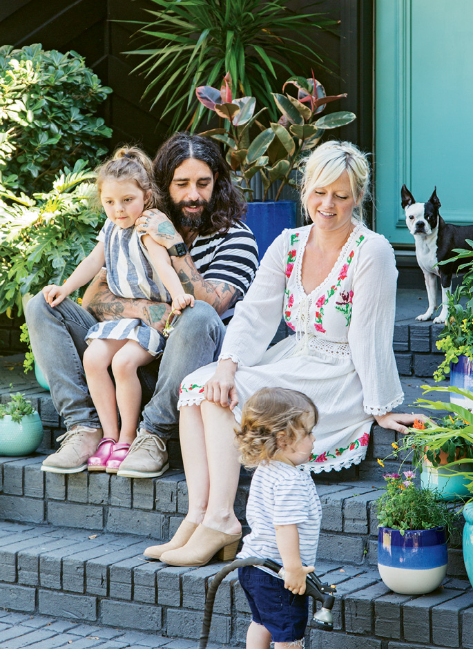 ROCKING THE SUBURBS: Erin and Creighton Barrett kick back on their front steps with Sunny, age five, and Bowie, almost two. To accommodate their growing family, the creative couple—he drums with Band of Horses, she's a textile artist—traded a cottage in Avondale for this roomier '70s ranch near Charles Towne Landing.