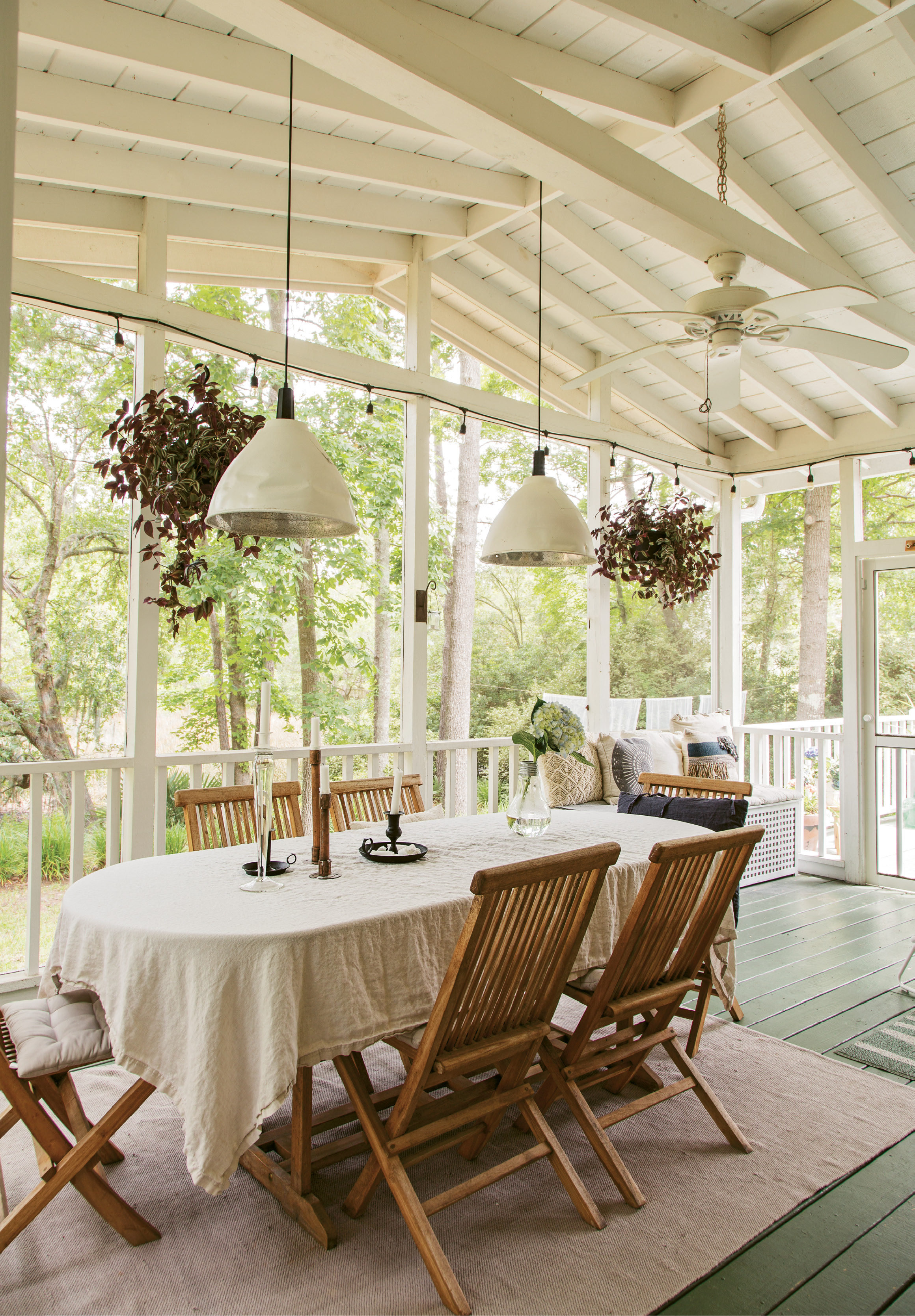 PORCH PARADISE: Winters in Gothenburg are harsh, so Therese and Jacob are loving the Lowcountry's mild climate. Mature trees and a long creek view make dining alfresco particularly pleasant, as do rustic wooden chairs, simple white linens, and soft light from pendant lamps and candles.