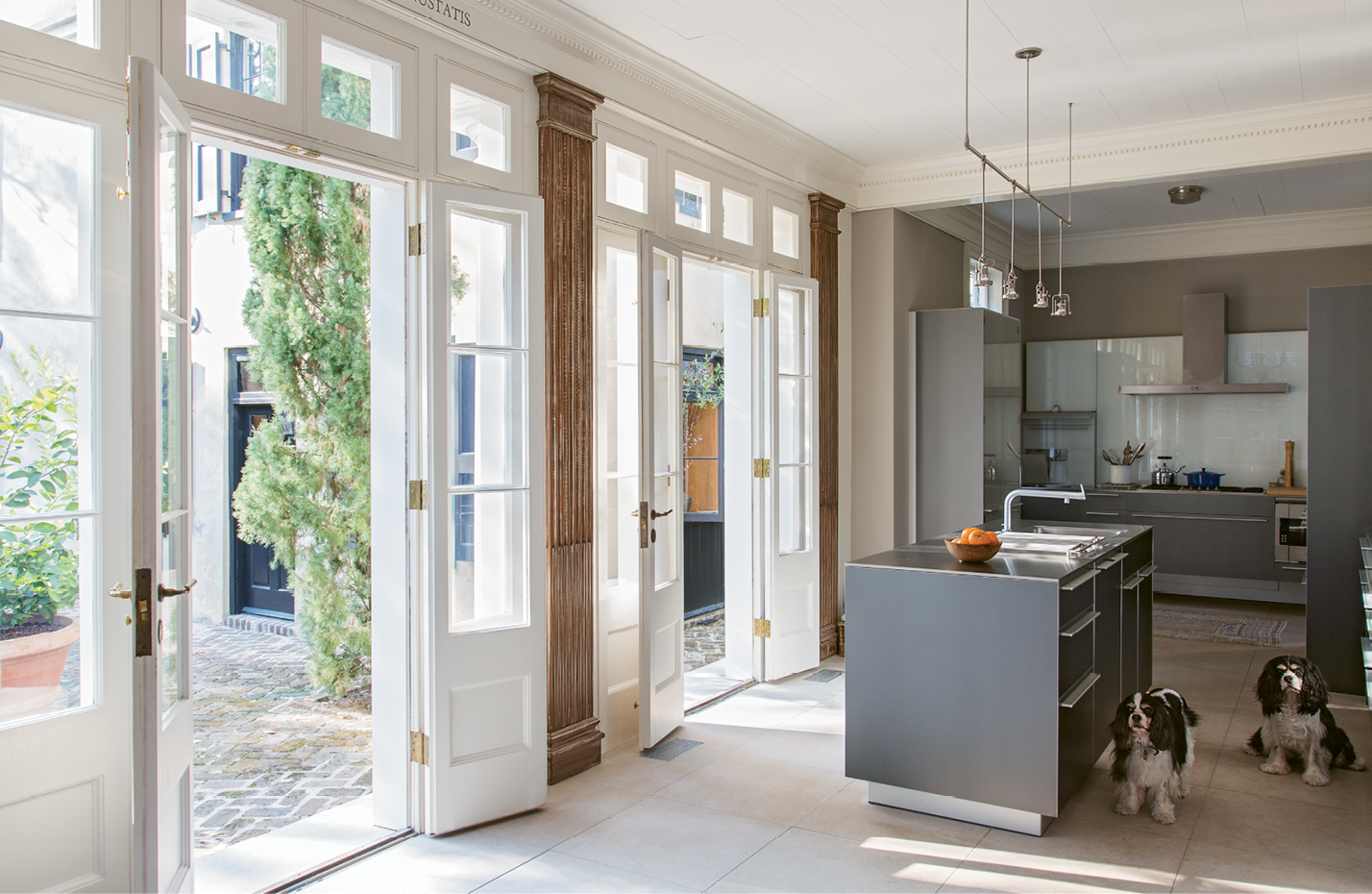 Sleek cabinetry by Bulthaup commingles with antiqued pilasters in the kitchen, located within what was once the rear porch.