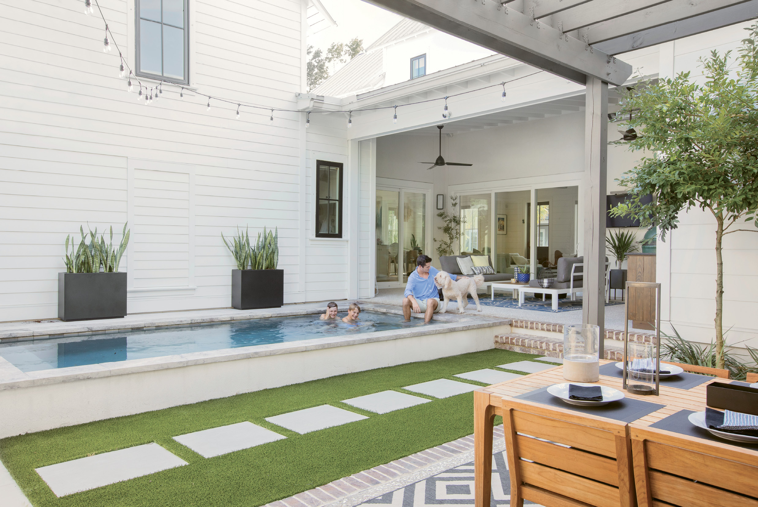 "Fun Zone: Three sliding glass doorways open to the outdoor entertaining areas, including a lounge space with aluminum and teak love seats from AllModern and a woven lantern from Lyndon Leigh, Cristian's ""kitchen,"" a compact pool where the boys and goldendoodle Kylie splash and play, and the pergola-covered dining area with a teak table and chairs."