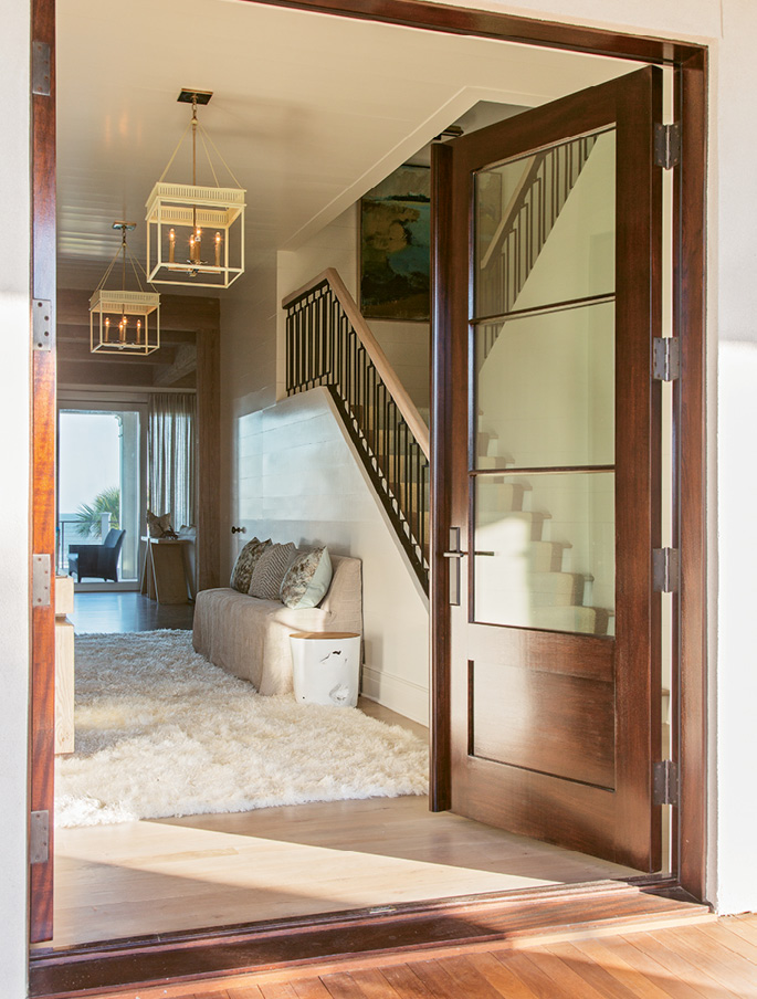 Upon stepping through the front door, guests are greeted with a direct shot to the back of the house, where a wall of windows provides ocean views.