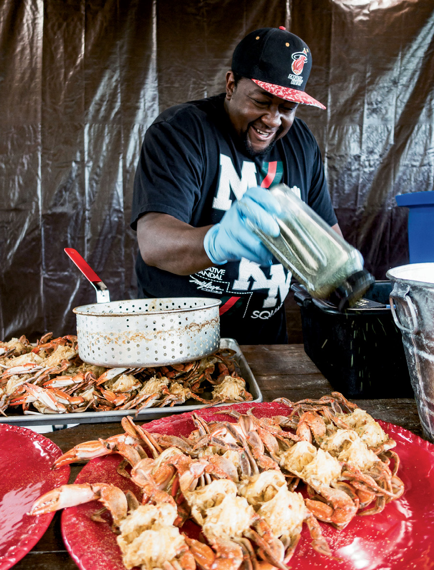 """For a gathering at Lady's Island Oyster Farm, Louis """"Granny"""" Albany shakes spices onto local blue crabs."""