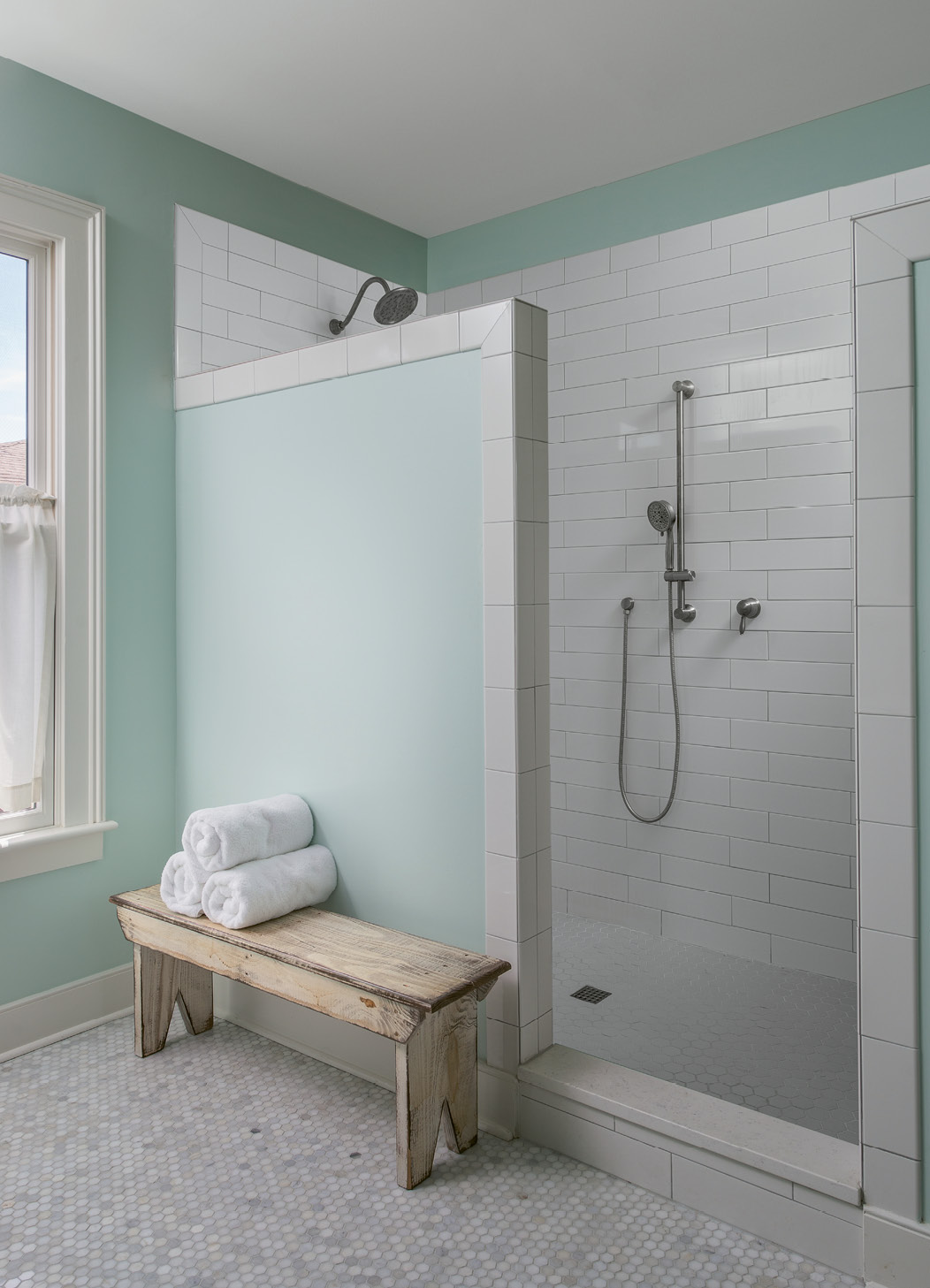 """A tiled shower with no glass door makes the bath low-maintenance. """"The design is a result of me hating to clean glass doors; I never wanted to see another squeegee again!"""" Cindy laughs."""