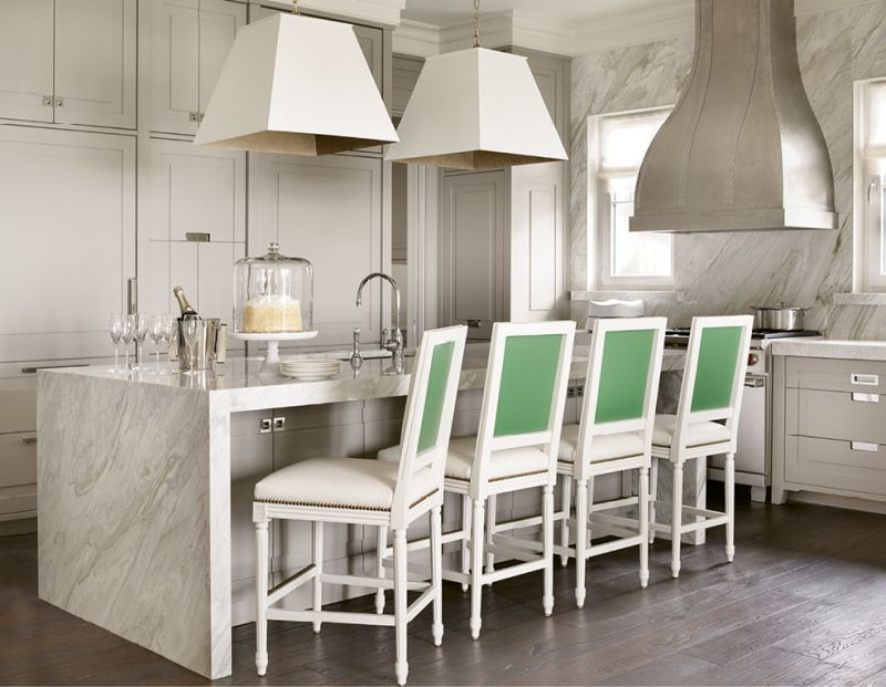 The kitchen sets a luxe tone with its walls and waterfall island wrapped in Calacatta Gold Extra marble as well as brass-lined light fixtures by Avrett, while custom chairs outfitted with white vinyl and green leather add graphic punch.