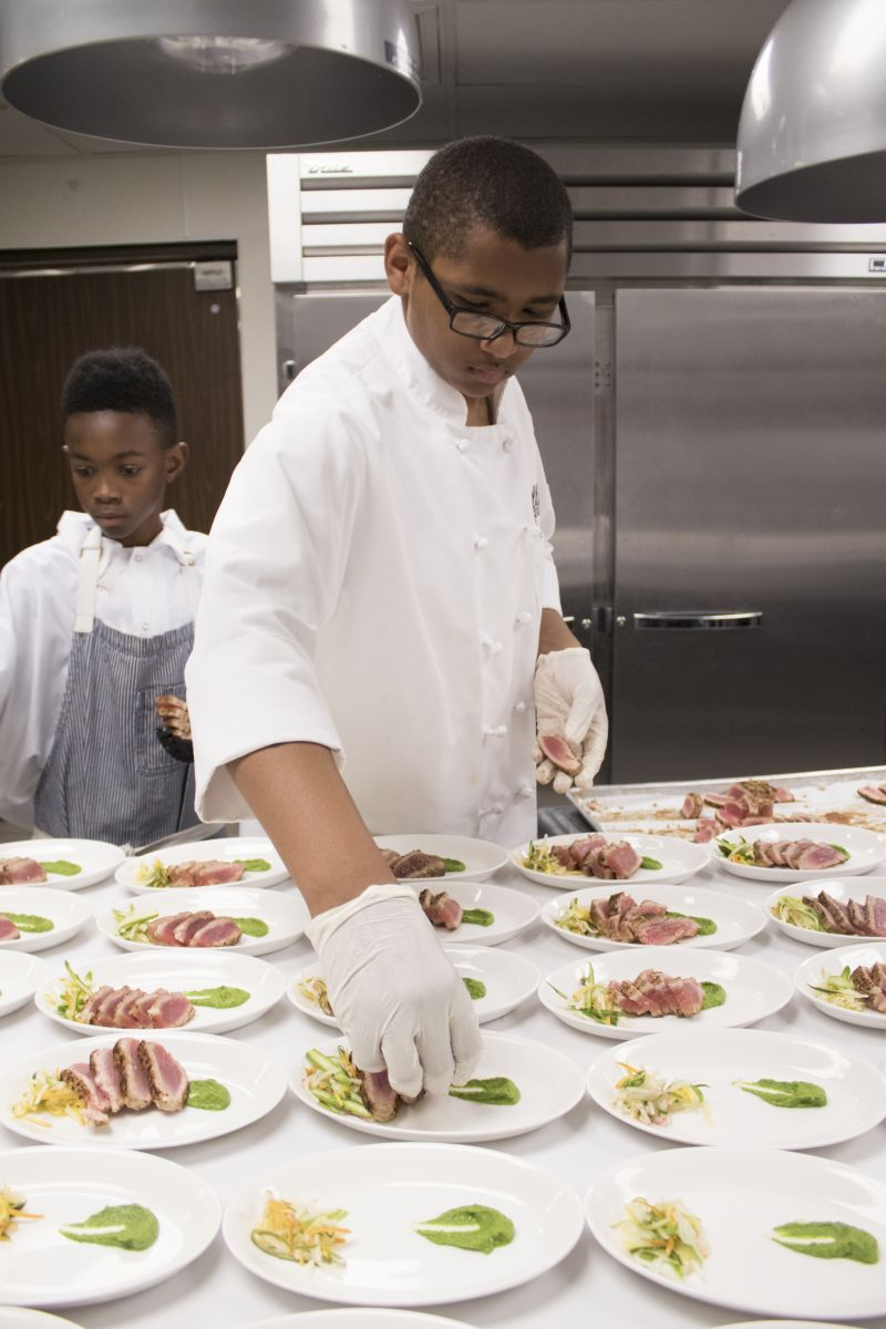 Aidan LaFave puts the finishing touches on the first course.