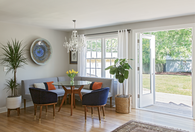 GATHER 'ROUND: Up to seven can fit comfortably in the West Elm-clad dining nook. When hosting a large group, Rachel simply swaps this glass tabletop out for a larger version. Pottery Barn drapes, a chandelier from Carolina Lanterns and Lighting, plants from Hyams, and a bowl hand-thrown by Louisiana artist Craig McMillan finish off the space.