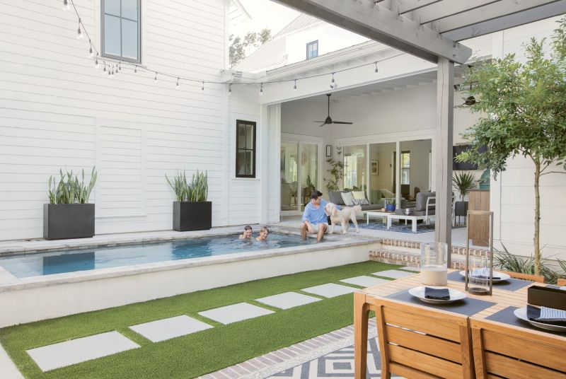 """Fun Zone: Three sliding glass doorways open to the outdoor entertaining areas, including a lounge space with aluminum and teak love seats from AllModern and a woven lantern from Lyndon Leigh, Cristian's """"kitchen,"""" a compact pool where the boys and goldendoodle Kylie splash and play, and the pergola-covered dining area with a teak table and chairs."""