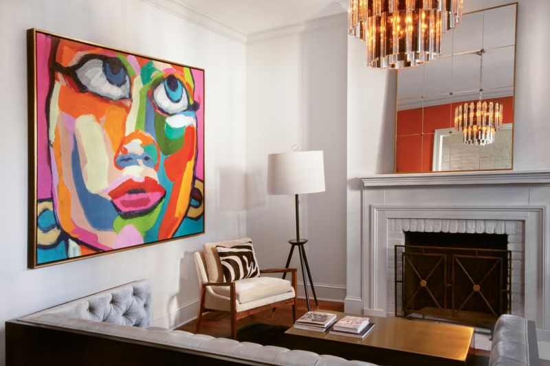 Balancing Act: In Dr. Eddie Irions's living room, a few bold statement pieces—such as a colorful portrait by Brazilian artist Robson Reis Marques and an Art Deco chandelier—are grounded by a mostly neutral palette.