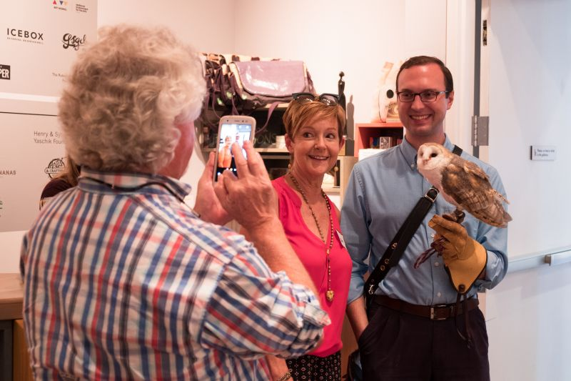 Gerri Greenwood poses with the owl while her husband, Linn Greenwood, snaps a photo.