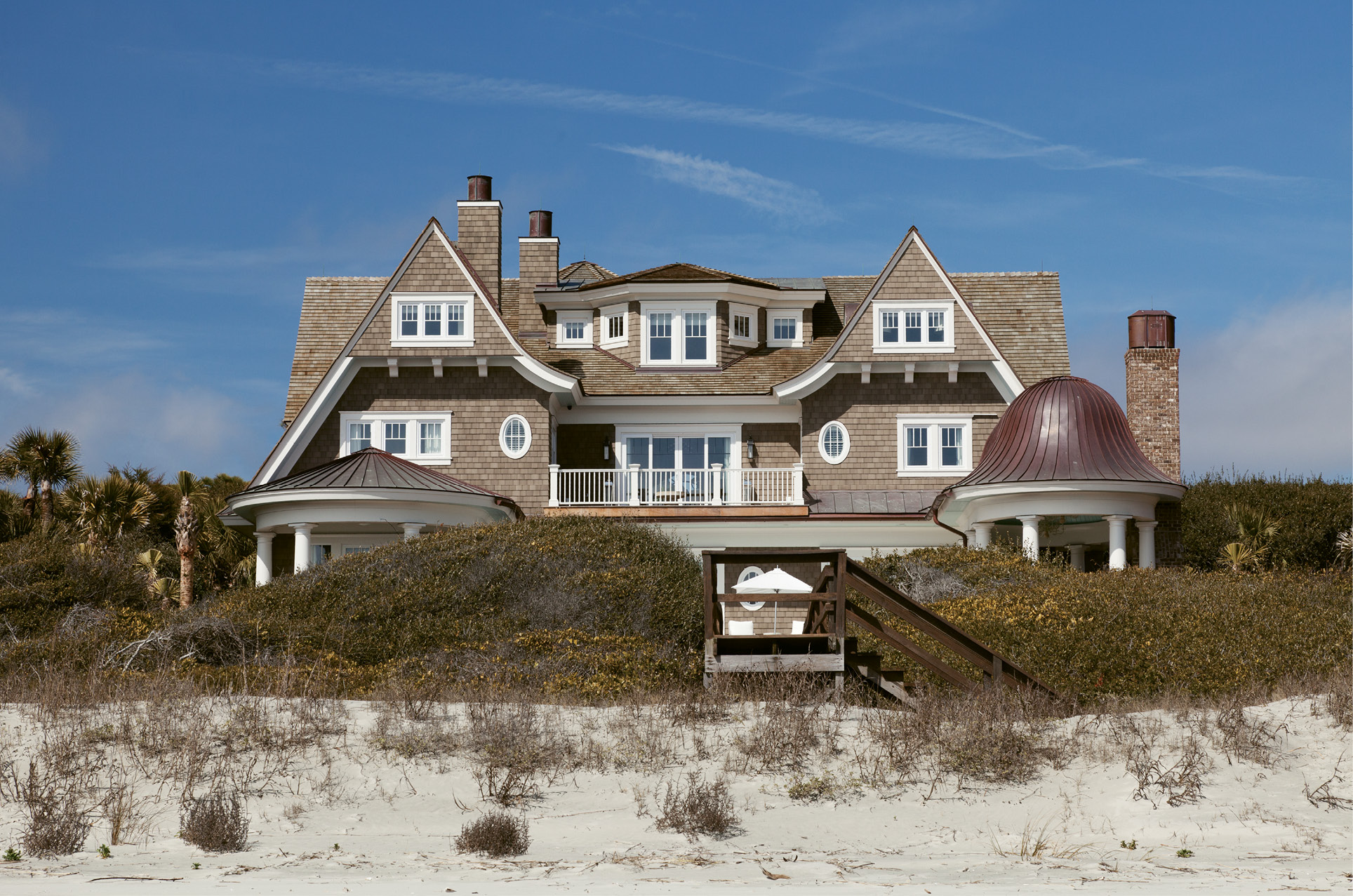 The rear overlooks sand and shore.
