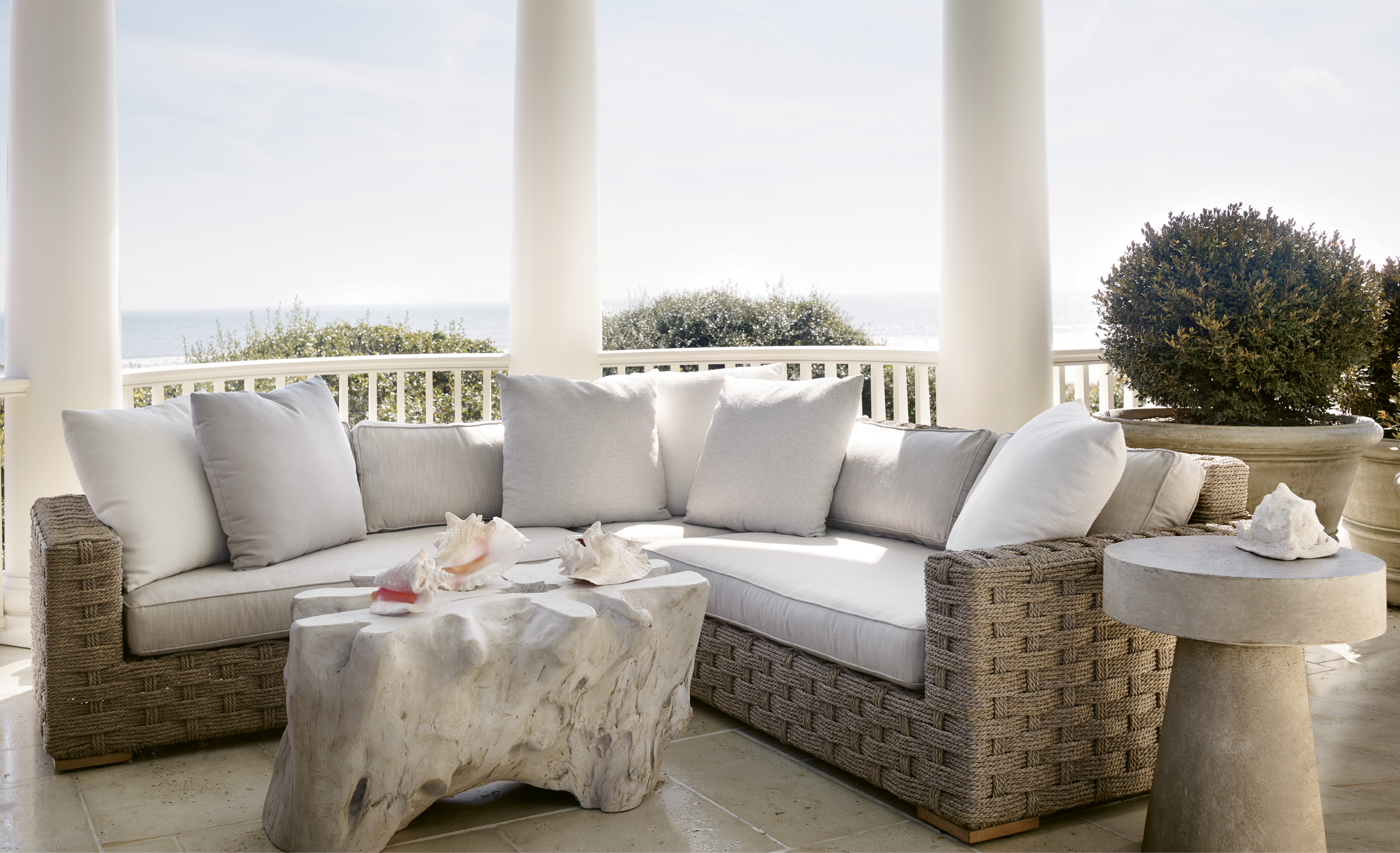 """This columned porch provides both privacy and panoramic views. """"The curved porches and their roofs shield the house from the neighbors, so you feel like you're in the only house on the beach,"""" says architect Chris Rose. The outdoor furnishings, including a Restoration Hardware rope sectional, were selected to echo the classicism and Cape Cod influence of the architecture."""