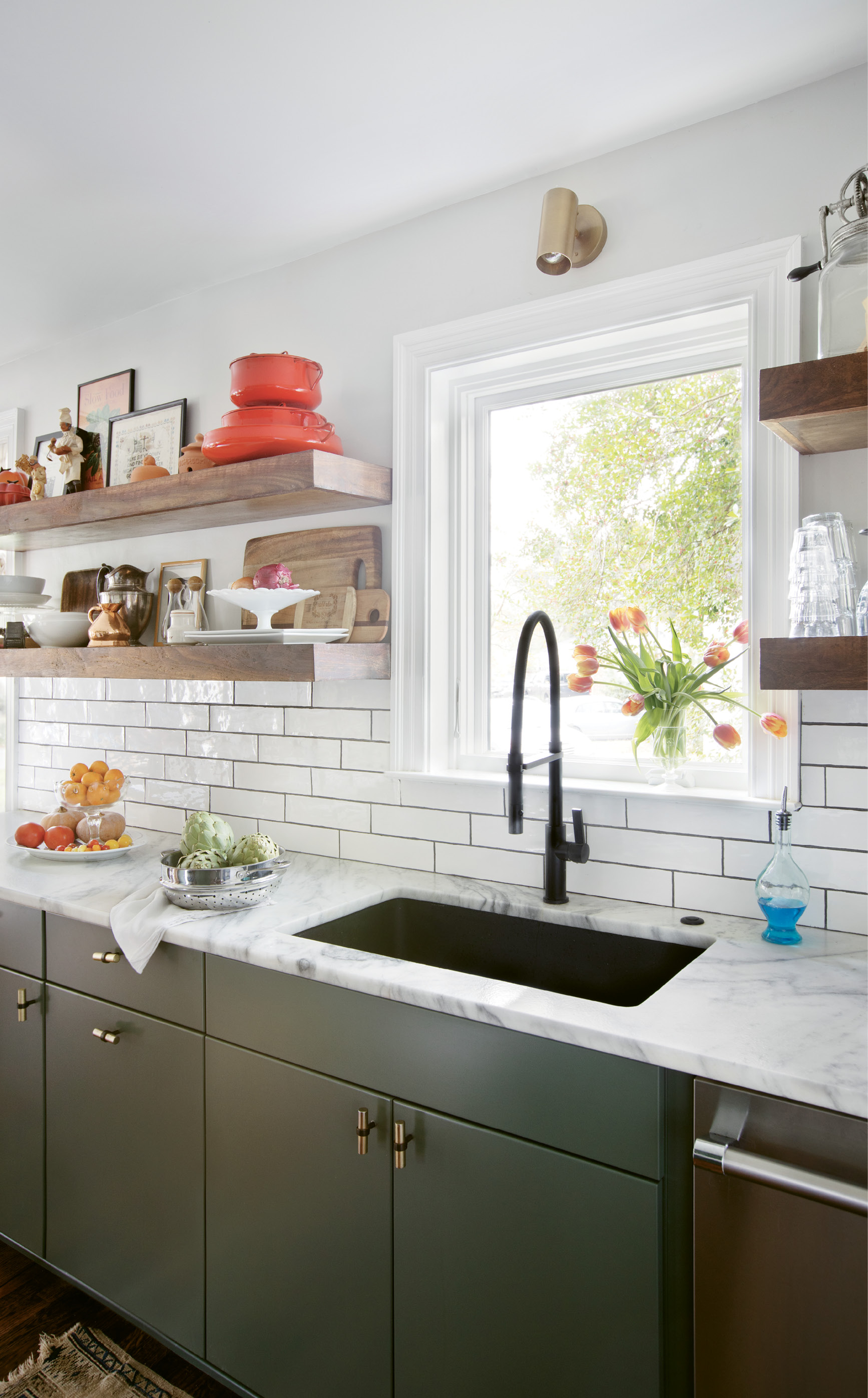 "WHERE THE MAGIC HAPPENS: Thanks to the removal of a wall between the kitchen and living room, cooking for guests is no longer claustrophobic. The refreshed space makes good use of local materials, including the faucet from Molufs and painted concrete backsplash from Palmetto Tile. ""Tile can really make a space without being too distracting,"" Carrie notes. Quartzite countertops, flat-face cabinets, and hardware from Anthropologie add to the clean look, while a rotating display of objects provides the finishing touch. ""We love the open shelves, and I find I'm always rearranging and shuffling things around; it is really inspiring to see fresh produce and artwork in the kitchen,"" she continues."