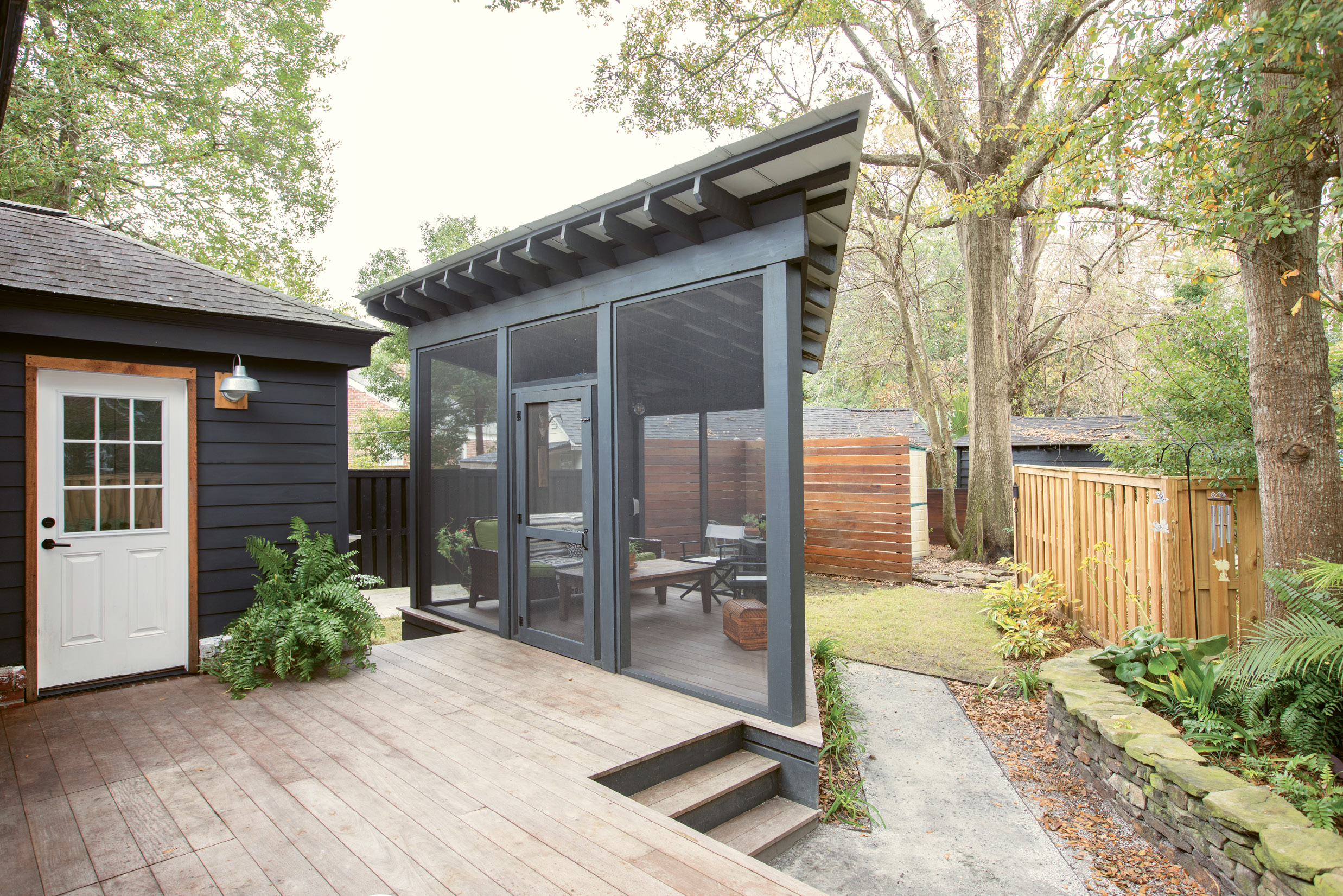 "PRIME PERCH: Just off the back deck, an angular screened-in porch makes the most of the triangular lot; its tin roof adds an industrial touch that feels perfectly in step with the rest of the modern-minded renovation. ""I'm so glad we made the screened-in porch happen: I love being outside, but the no-seeums drive me nuts,"" Jacques says. ""There's nothing better than sitting on the couch outside, listening to the wind blow, birds sing, and children playing in the neighborhood."""