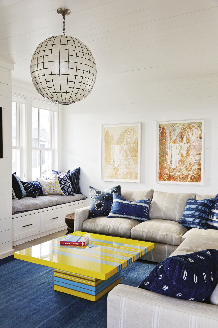 The family room hangs 10 with a bright yellow and blue surfboard-inspired table and an array of pillows made from vintage textiles. Delicious artwork by Matthew Brandt is made of Gummi Bears and Pixy Stixs.