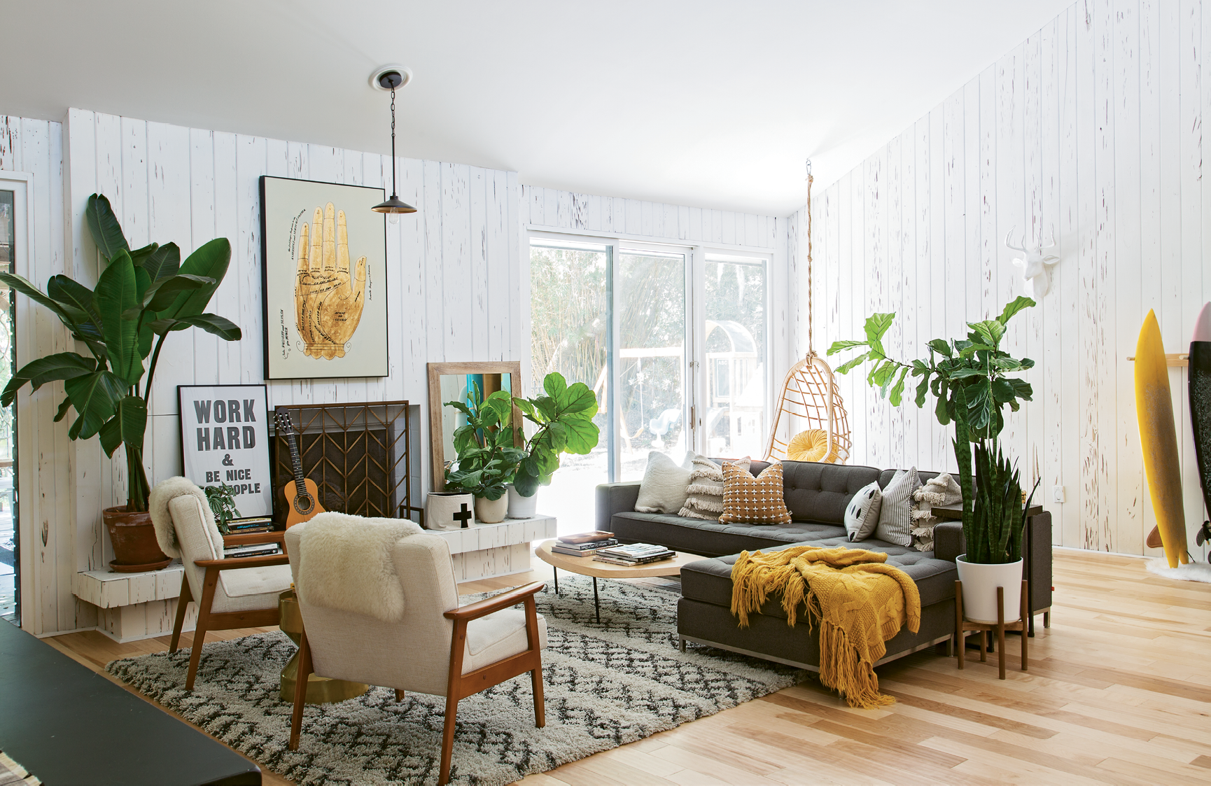 The duo revamped the living room by whitewashing existing pecky cypress walls, swapping red laminate flooring for hardwoods, and adding California-cool furnishings and accessories.