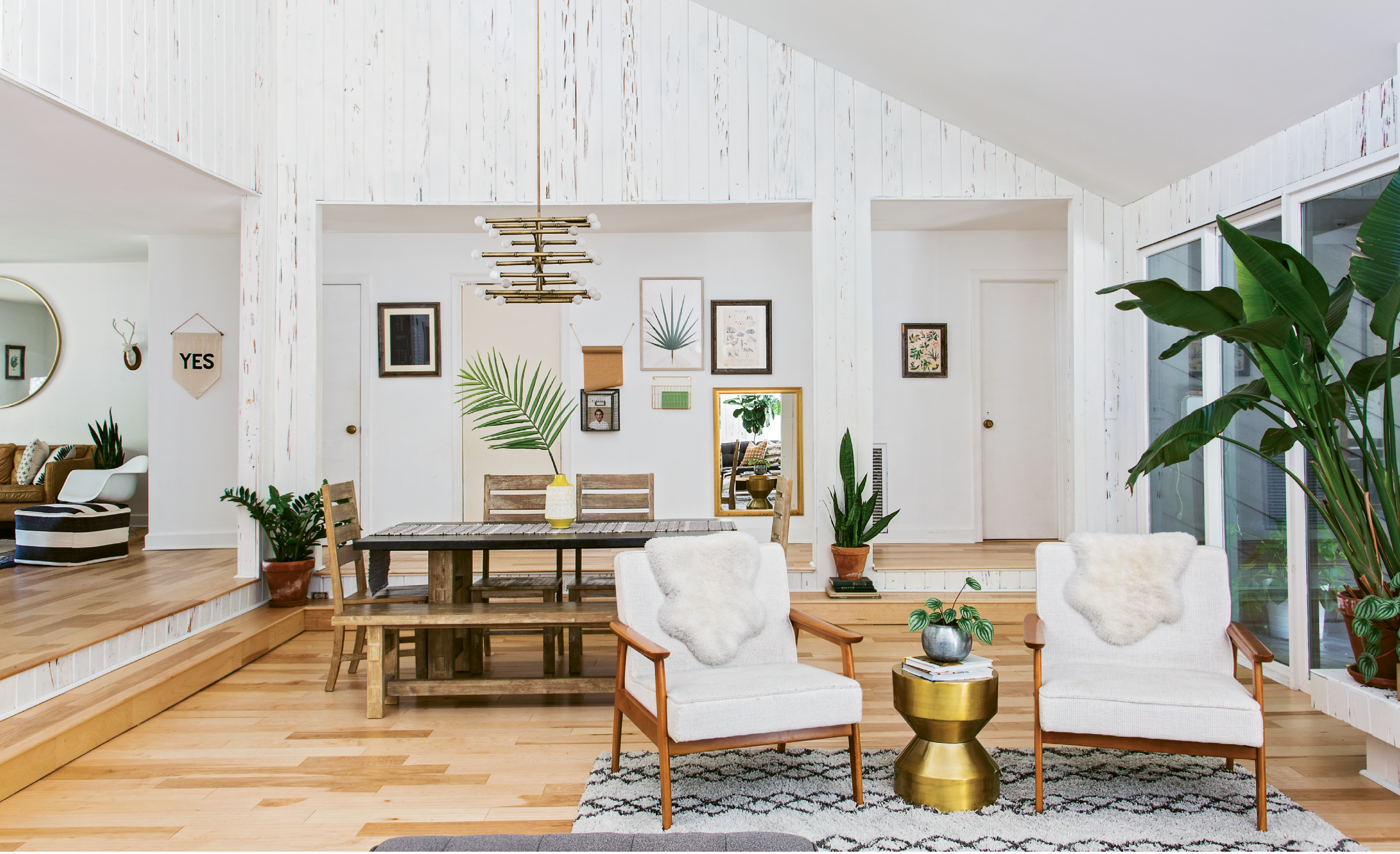 LUXE LOOKS: After almost splurging on a Jonathan Adler chandelier, Erin spotted a similar piece for less than $100 on Overstock.com; the steal now hangs over the dining room table. House plants and botanical prints complement the wood grain in the original pecky cypress walls.
