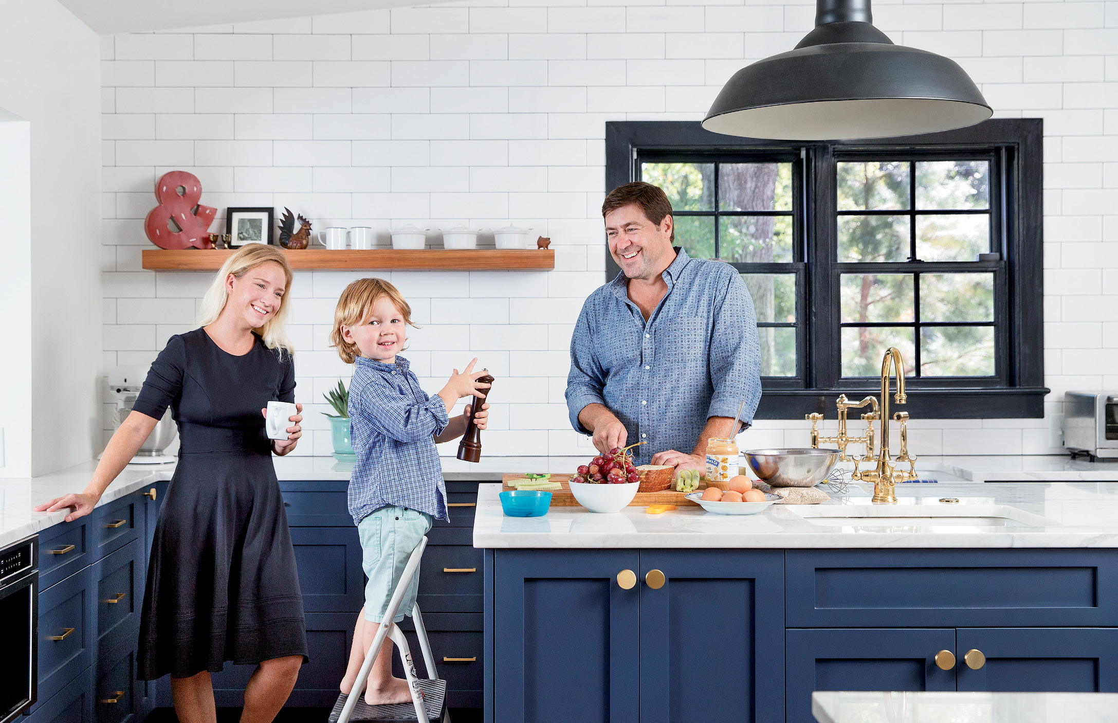 family style: When Mike and Emilee Lata bought the centuries-old abode, the kitchen was outdated, with low ceilings and a lack of natural light. The couple (pictured here with son Henry) worked with David Thompson Architects and Renew Urban to take the cooking space down to the studs and redesign it with a luxe farmhouse vibe.