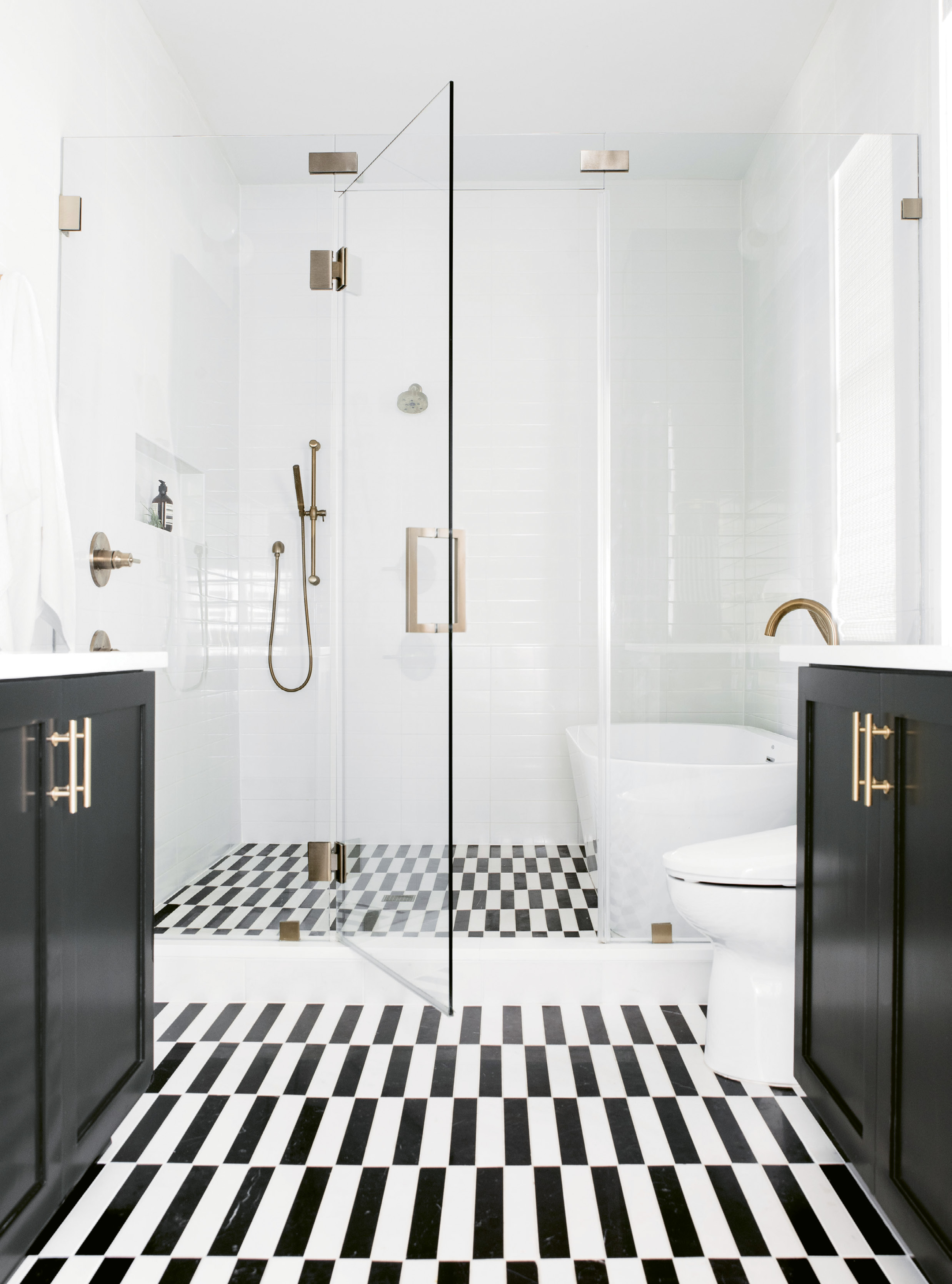 "CLEAN & SERENE: The master suite rivals boutique hotels for its comfort and style. A space-saving ""wet room"" configuration in the bath fits a walk-in shower and soaking tub, while glistening white-tile walls, cabinets covered in Benjamin Moore's ""Black Beauty,"" and a custom-cut marble tile floor add drama."