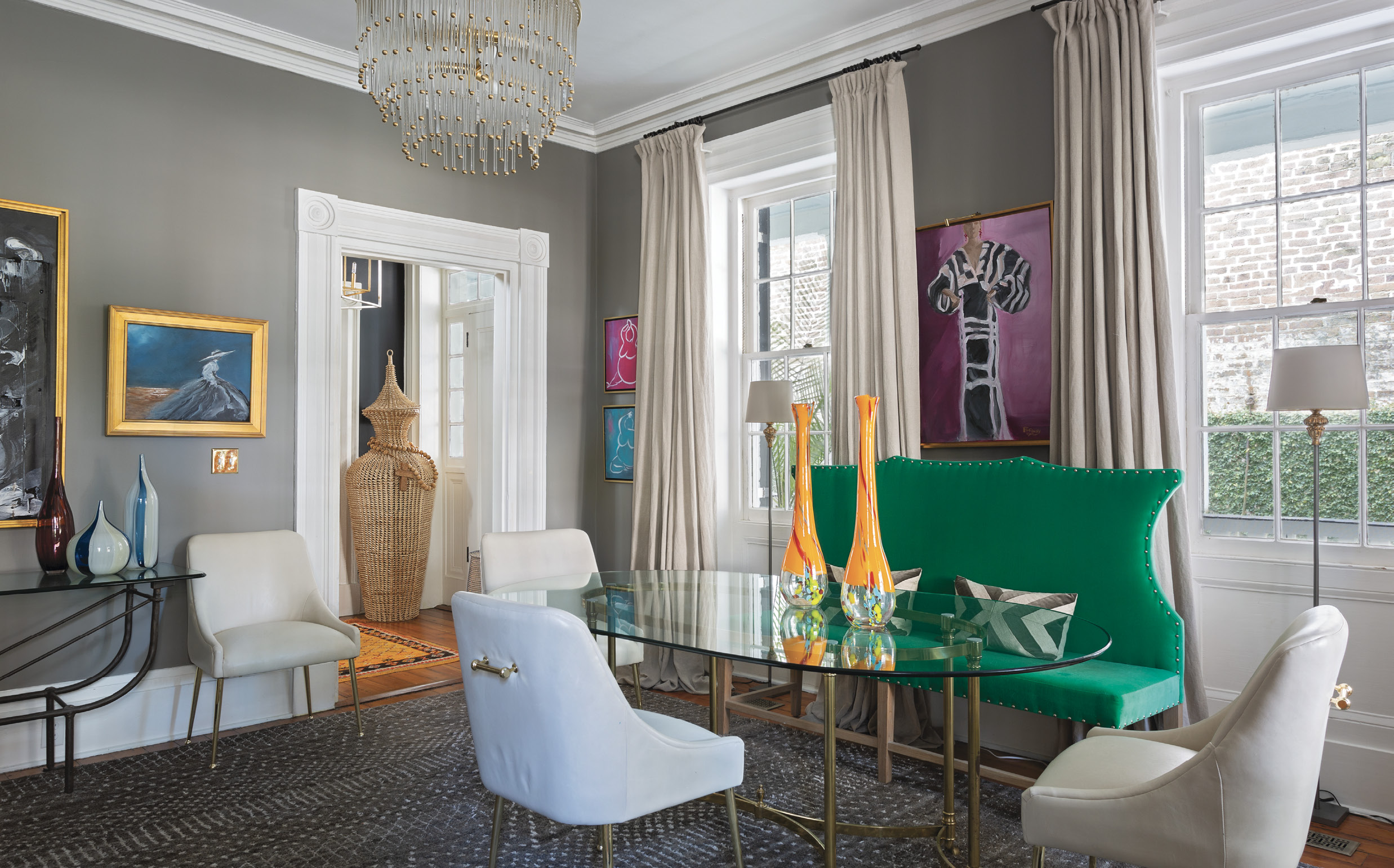 Something Old, Something New: Bold colors, eclectic art, contrasting fabrics, and a smattering of antiques turn a formal sitting room into a dynamic space. The glass dining table from Patricia Allen Antiques at Fritz Porter dispenses with formality, thanks to white leather chairs from Anthropologie and a green velvet settee from South of Market downtown.