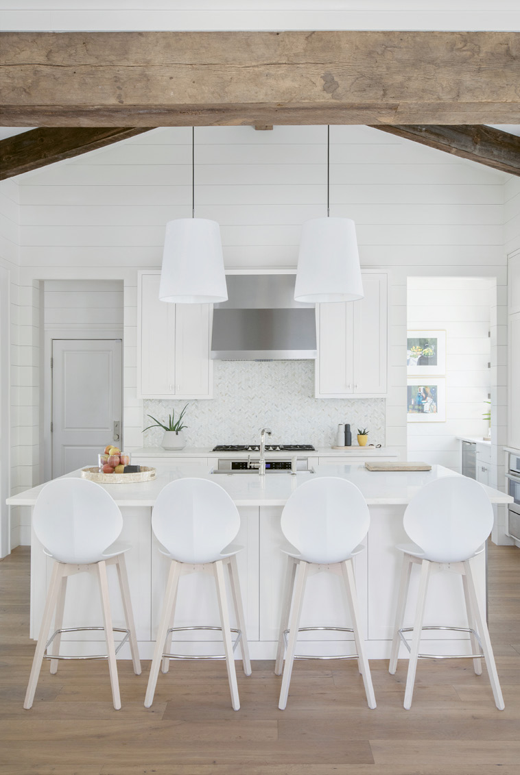 In the streamlined kitchen, seamless cabinetry on each side of the expansive marble-topped island holds everything from cookware to craft supplies, as well as a built-in beverage cooler for kids' drinks. To the right of the chevron-tiled backsplash, a walk-in pantry houses cooking staples and the wine bar.