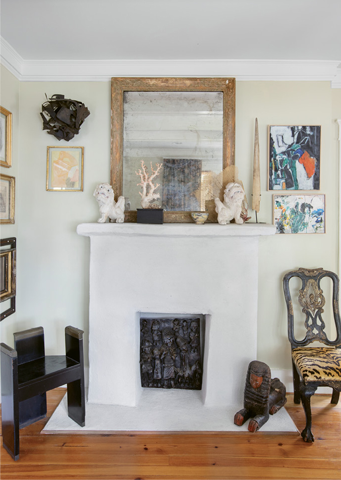 """in the mix: In the parlor, Debbie had the fireplace surround stuccoed and painted white for a clean, smooth effect that better showcases the melange of artwork and interesting objects she deems a """"necessary excess."""""""