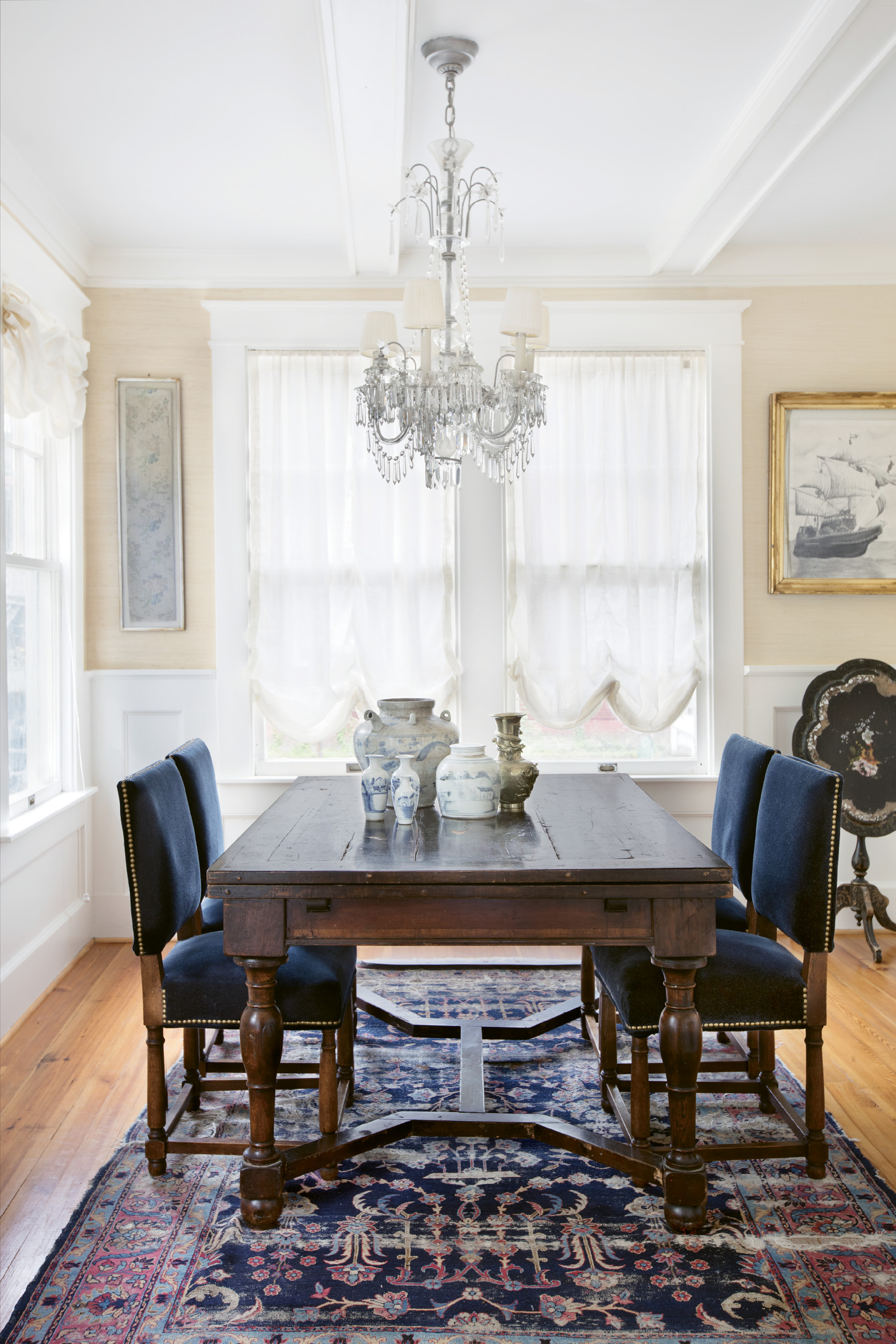 In the Navy: Deep blues and neutrals set the tone in the dining room, where the chairs are upholstered in blue mohair. The artwork includes a framed Chinese embroidery remnant as well as a pencil drawing of a naval ship that Melvin completed in high school. Debbie found it during one of their moves and had it framed in honor of his years of Navy service.