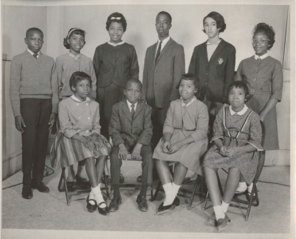 "The First Children: Though doors opened for Millicent and her 10 fellow plaintiffs—(pictured from left to right, standing) Clarence Alexander, Barbara Ford, Jacqueline Ford, Ralph Stoney Dawson, Millicent Brown, Clarice Hines, (and seated, left to right) Cassandra Alexander, Gerald Alexander, Gail Ford, Oveta Glover, and (not pictured) Valerie Wright—to attend peninsula public schools in September 1963, many faced ostracism, and worse. ""Some of the others were much younger than I was,"" says Millicent, who still feels guilty for not being able to support her fellow Rivers High attendee, eighth grader Jackie Ford, whom she wouldn't cross paths with during the school day. ""They were more vulnerable than I was."""