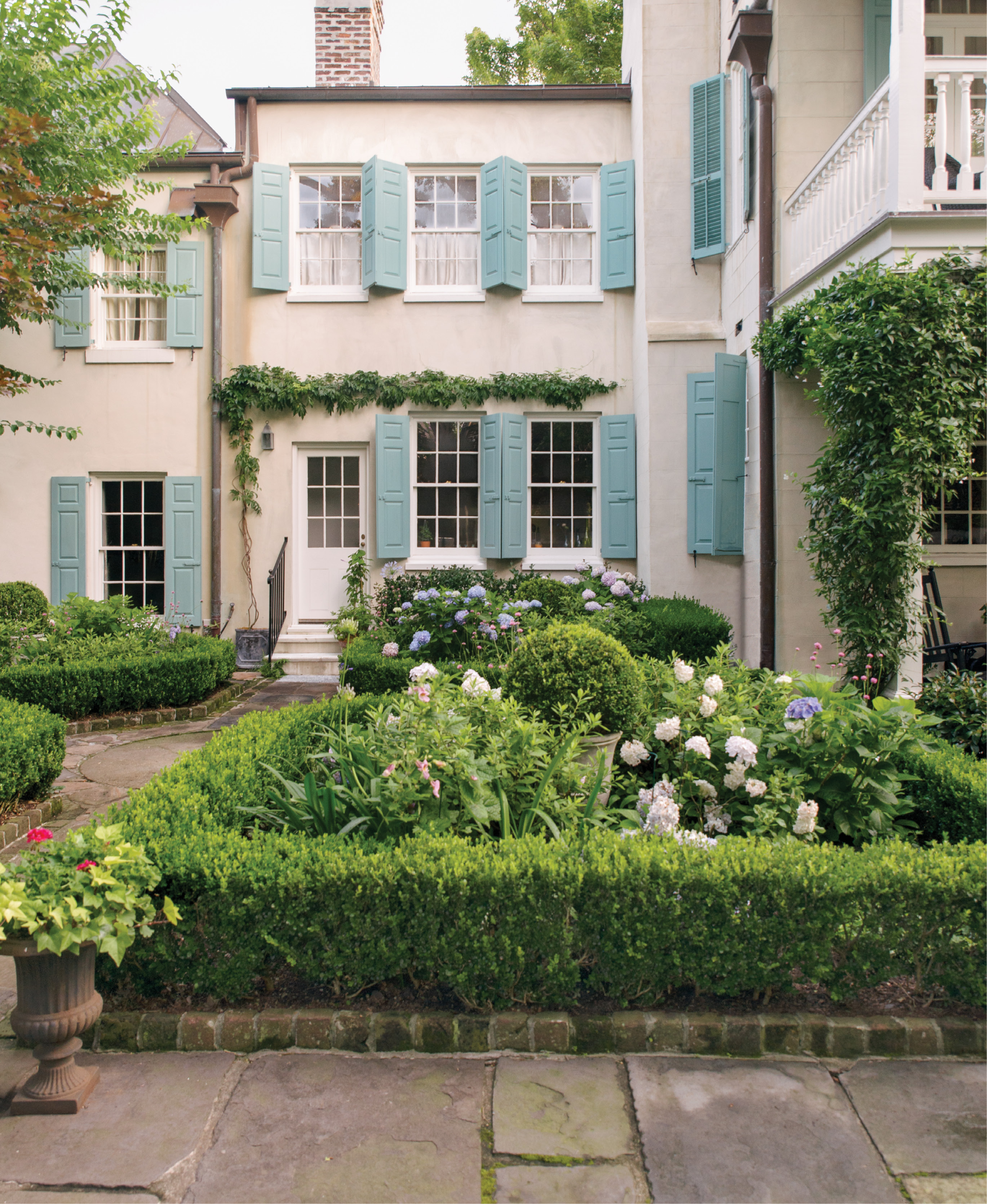 Each of the parterre's quadrants is trimmed in boxwood with a boxwood globe at the core. Flowering plants, such as agapanthus, azaleas, and hydrangeas, pop against the green. Monica potted a non-invasive evergreen wisteria to train above the kitchen door.