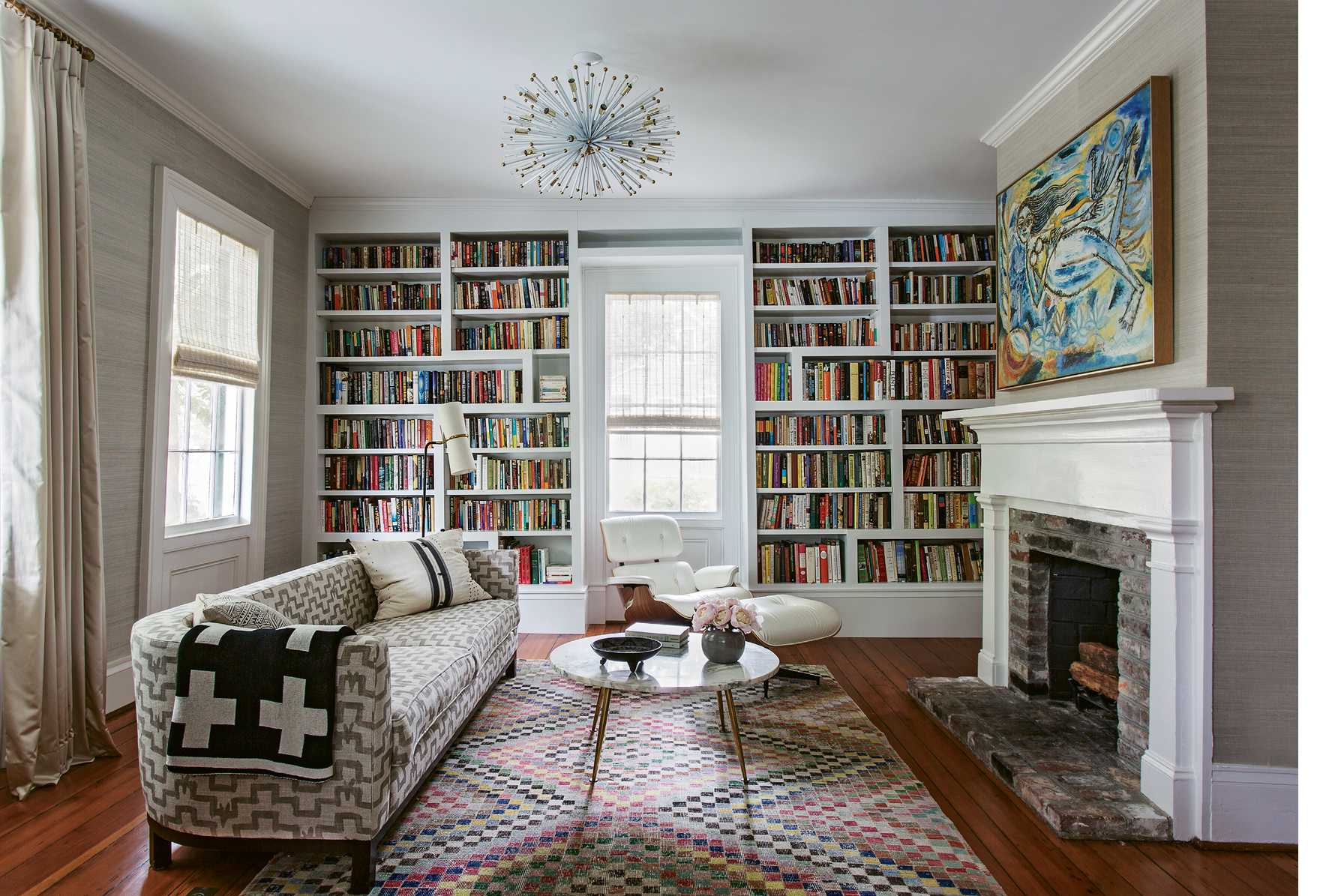 """PATTERN PLAY: In the library, a splashy yellow-and-blue painting by Indian artist Laxman Pai lives in harmony with a graphic pink rug and a patterned vintage sofa. Keenan says mixing textiles helps a home feel """"more lived-in and not so perfect."""""""