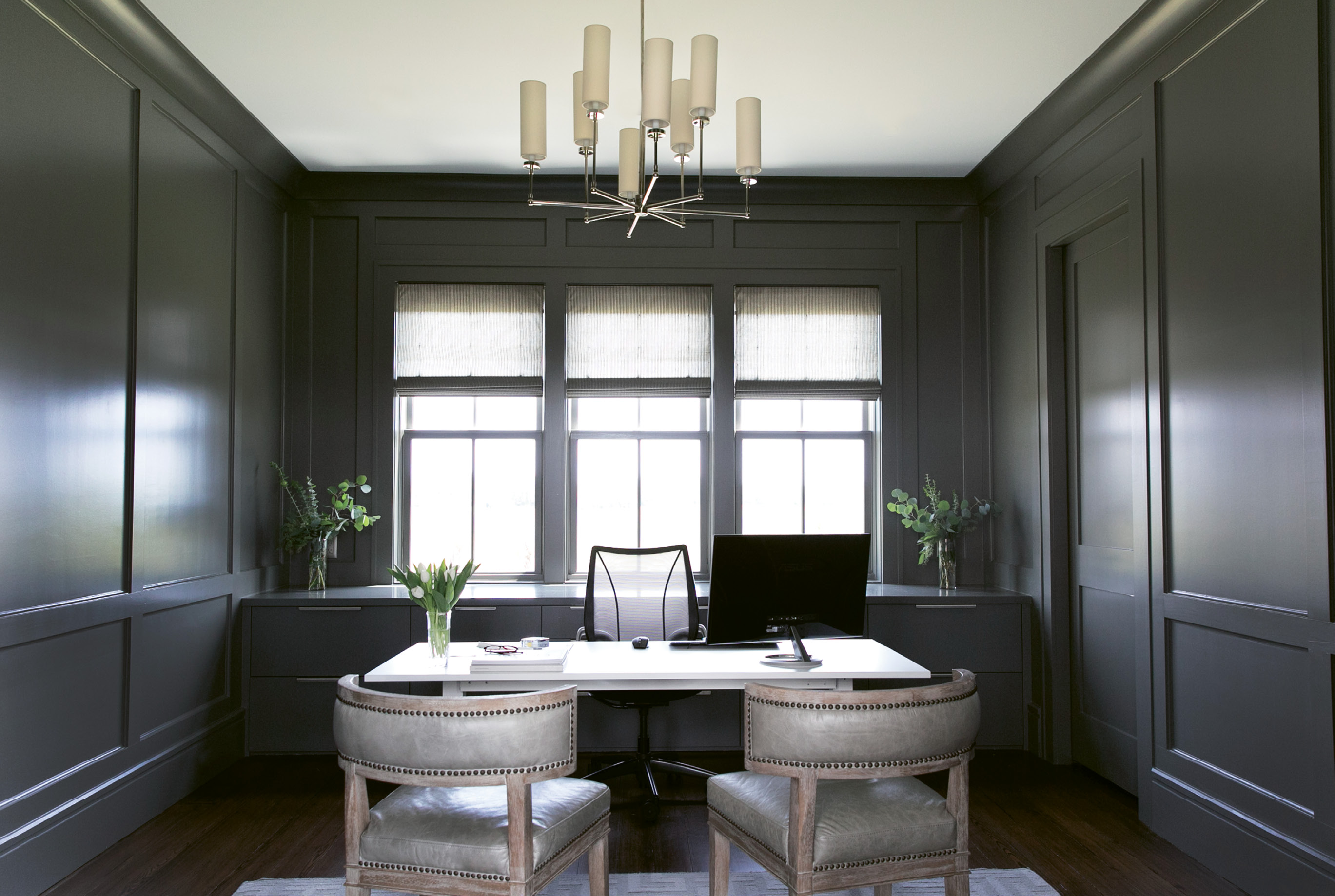 Dark grey walls cultivate a sense of calm and visually separate her work zone from the rest of the home.