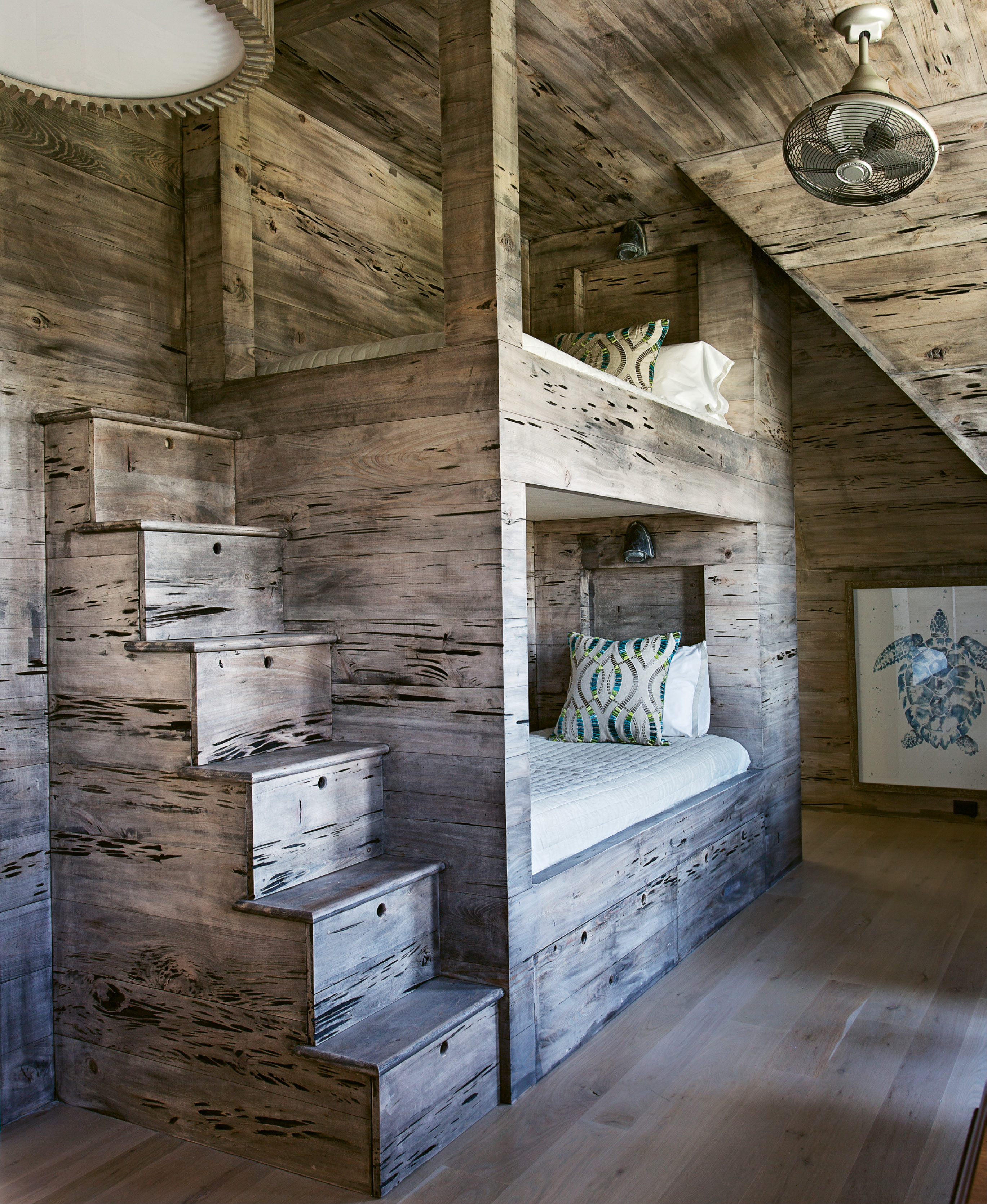 Pecky cypress walls warm up the bunk room, which boasts four beds and two en suite baths.