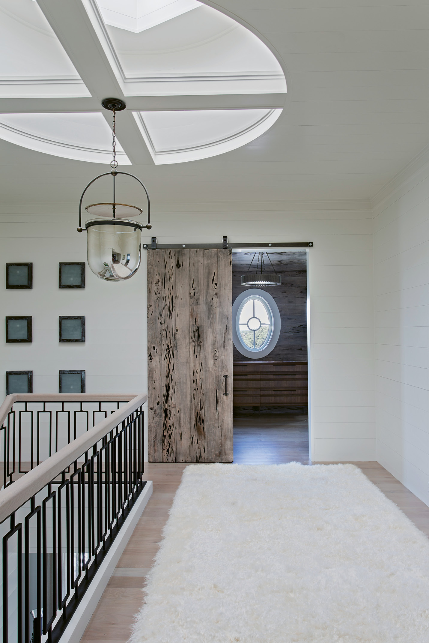 Haute Hallway: A medallion-shaped skylight presides over this second-floor hallway with a custom stair rail designed by David Smith.