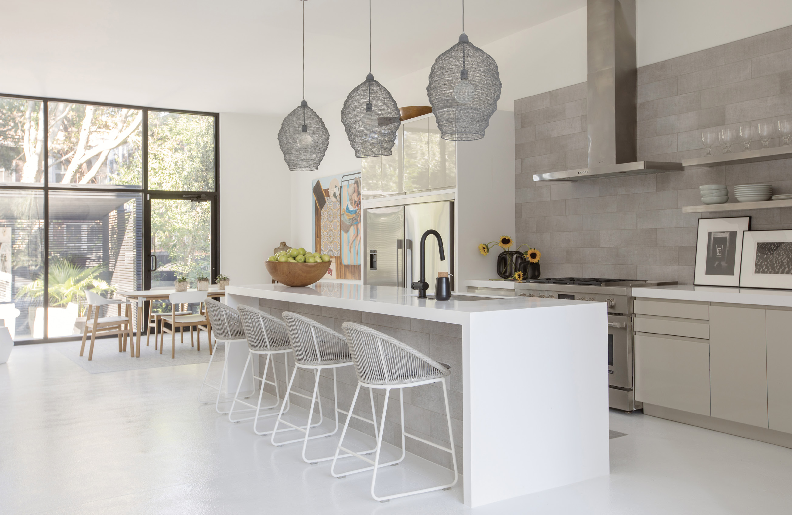 """WHITE SPACE: Mixing textures in white, black, and beige, the kitchen is Baldwin's quiet space. """"With the black exterior and all white interior, I was drawn to a middle ground, and that manifested in a neutral-toned kitchen,"""" she says. """"It allows you to have that burst of color as an offset."""" Wire pendant lights from Denmark tie in to the industrial feel of the retail-style doors and windows; Teak Warehouse stools complete the look."""