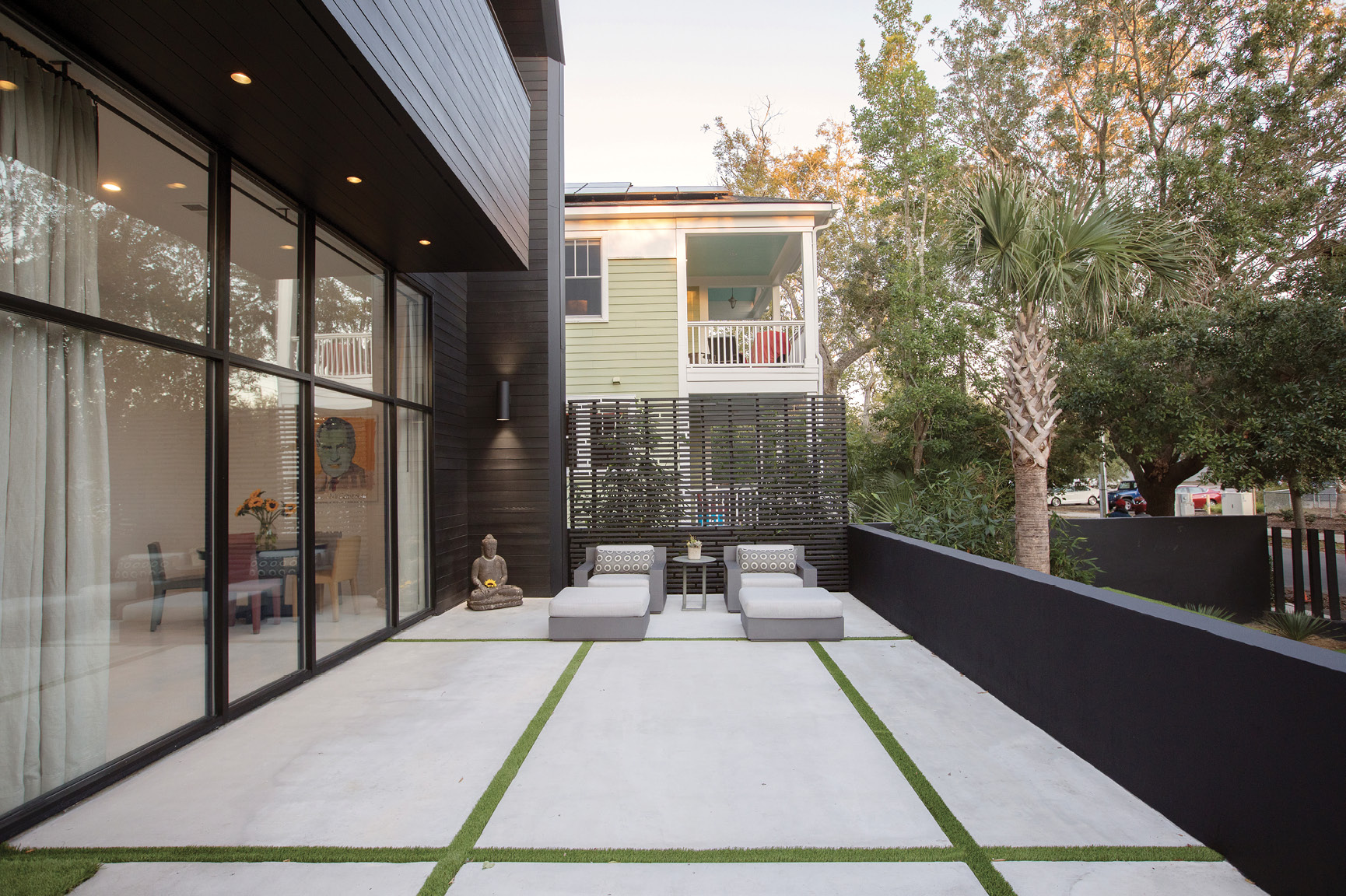 The front terrace strikes a contrast with the traditional porch behind it. Artificial turf between large concrete pavers soften the space, adorned by two Restoration Hardware lounge chairs.