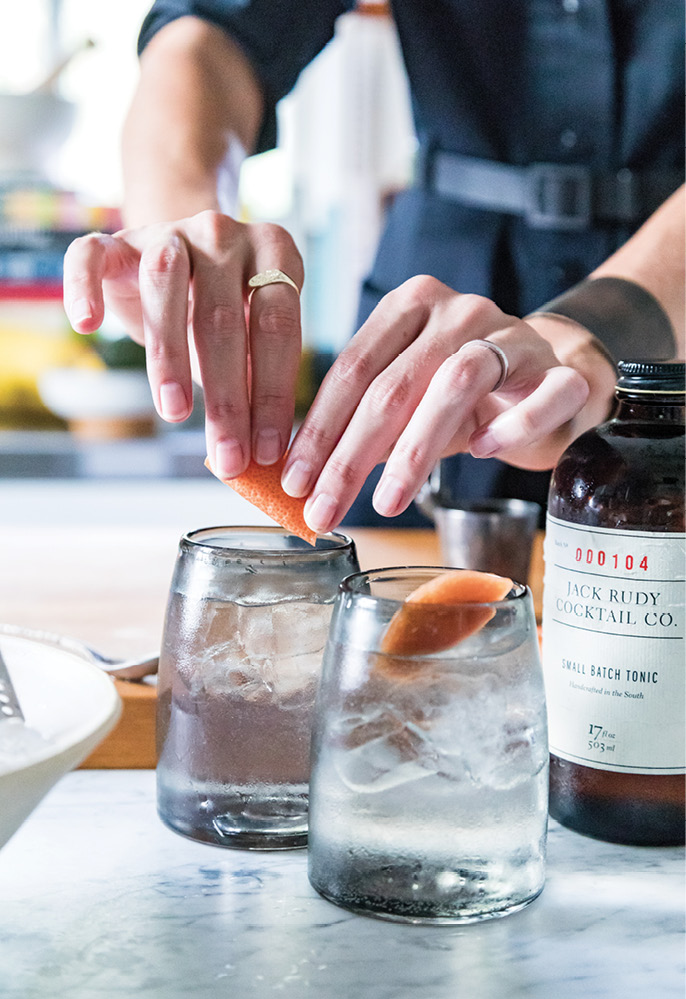 Erin mixes cocktails with 11/2 ounce Ethereal Gin, 1/2 ounce Jack Rudy Tonic Syrup, ice, grapefruit La Croix, and a grapefruit peel garnish.