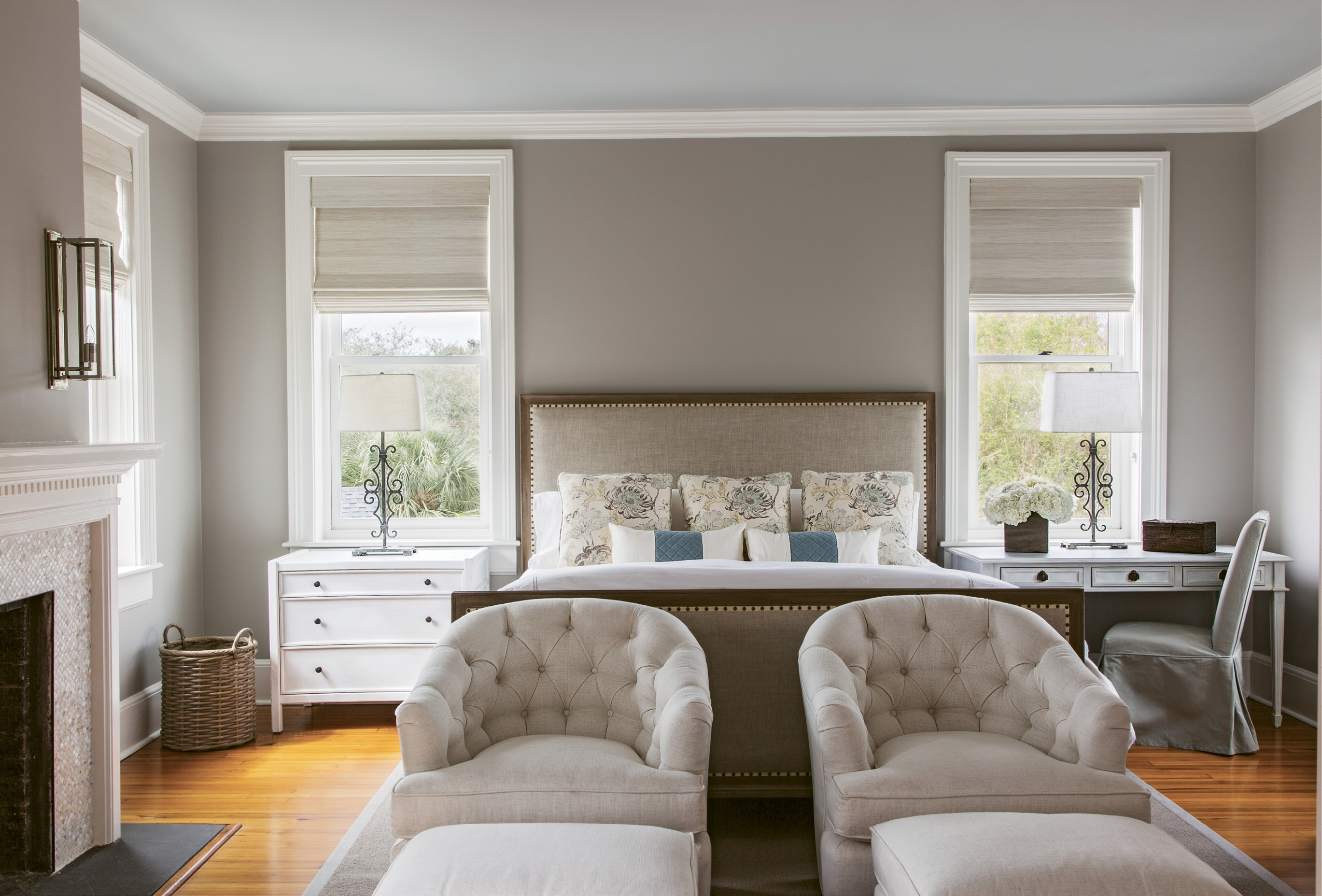"Neutral Territory: For the master bedroom, Peake worked with a neutral palette conducive to relaxation: Benjamin Moore ""Cumulus Cloud"" covers the walls, with ""Half Moon Crest"" on the ceiling. The custom headboard was upholstered in Belgian linen. Natural woven shades provide privacy while still allowing for natural light."