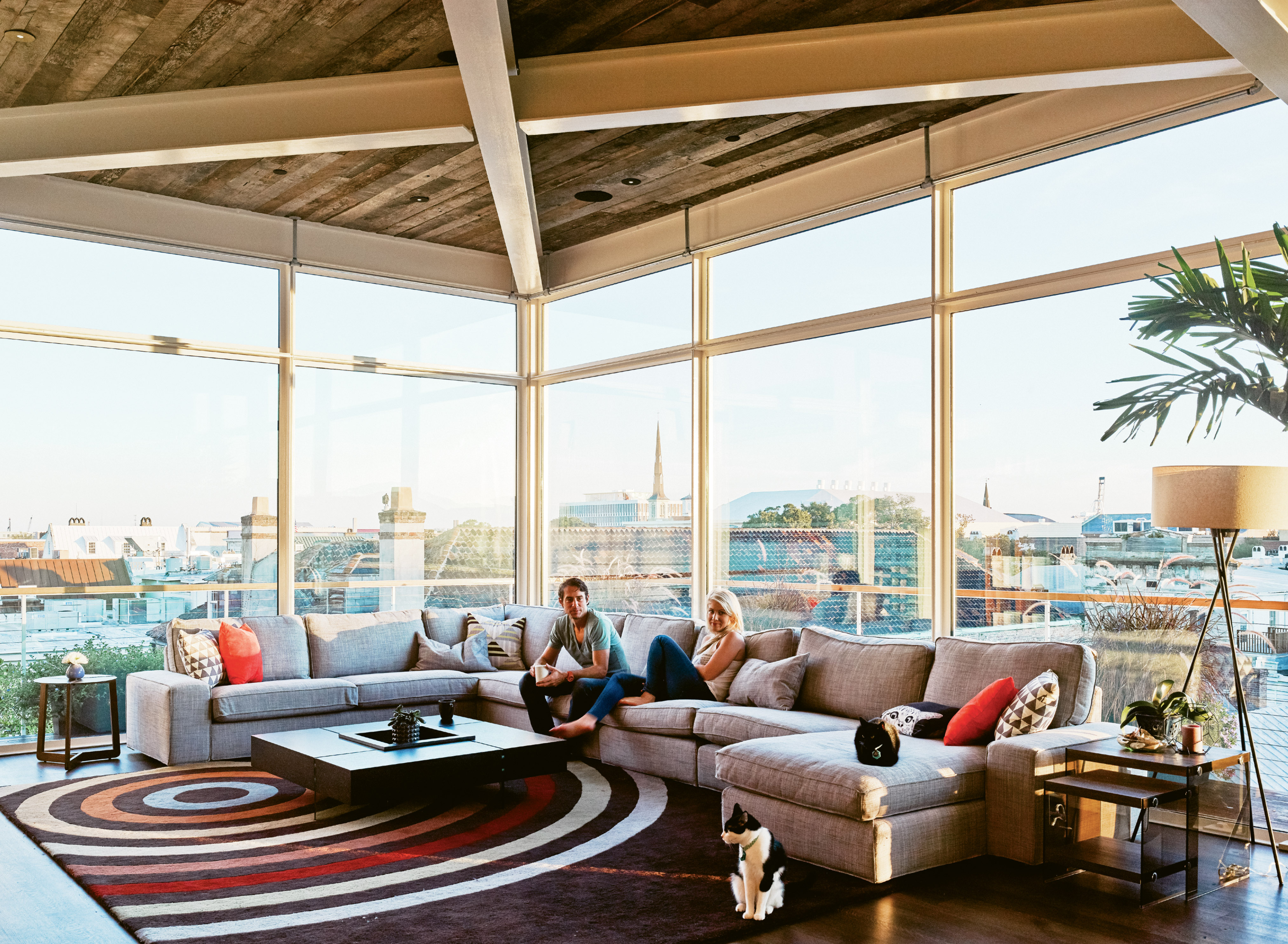 Yessian, pictured with girlfriend Arielle Stratton and cats Jean Michelle and Jean George, tackled the interior design himself, keeping the furnishings—such as this Ikea couch, West Elm lamp, and All Modern rug—minimal and letting the views take center stage.