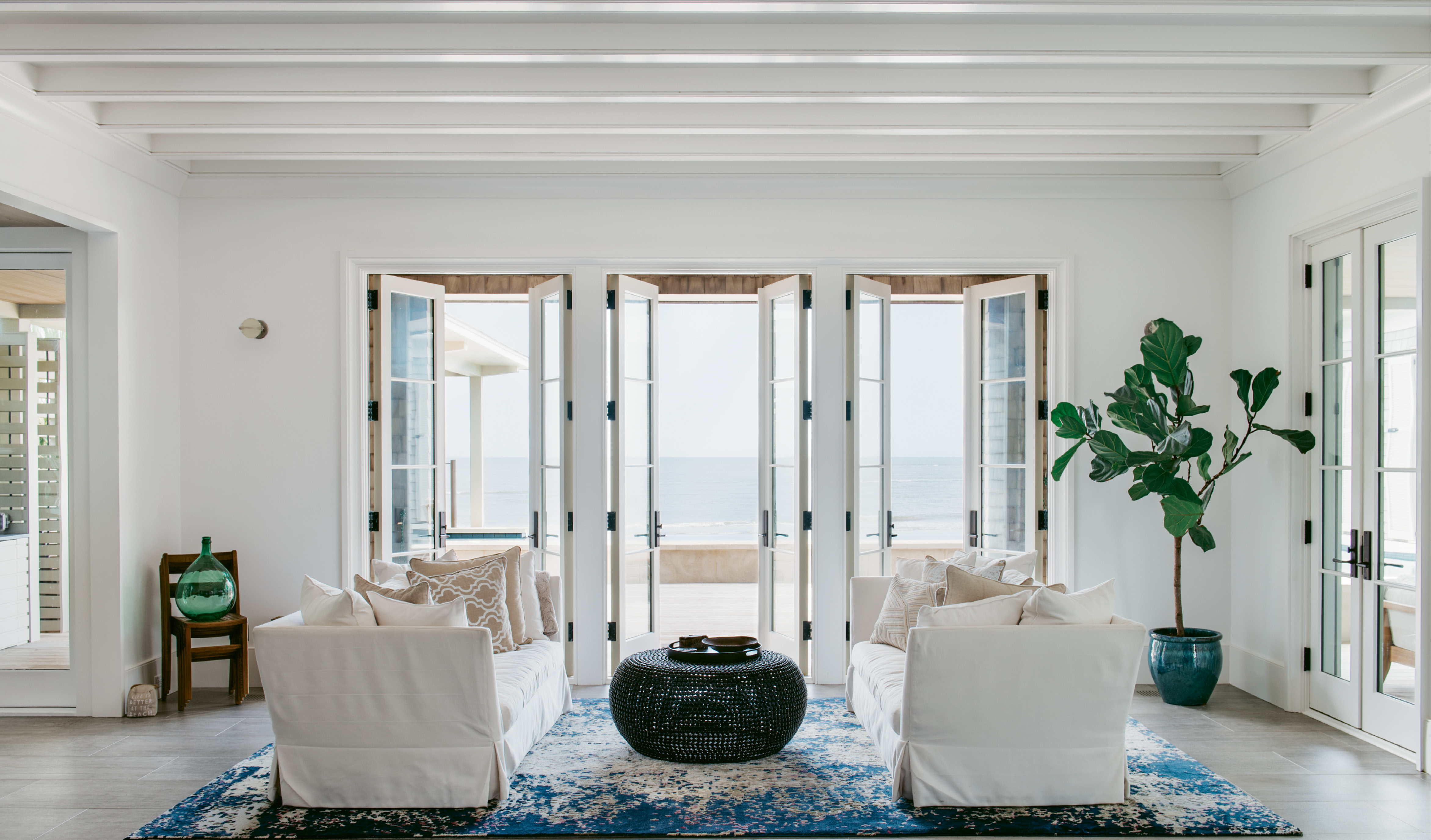 The living room is appointed with pieces in a coastal palette—such as a pair of neutral couches by Cisco Brothers and a custom blue and white rug by J.D. Staron—that don't distract from views of the pool and the ocean beyond.