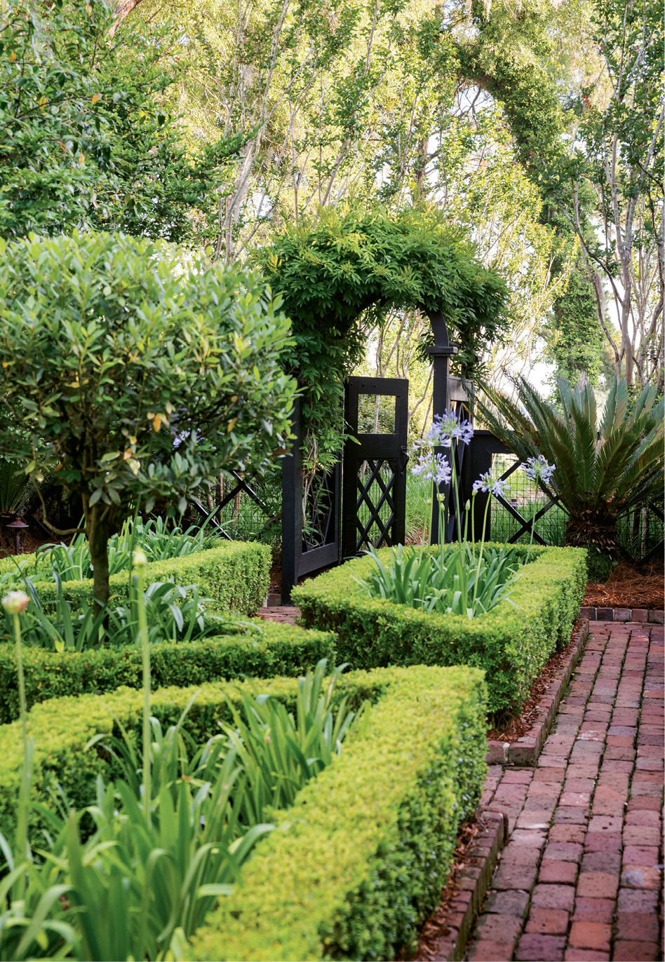 River Walk: A gateway offers an invitation toward the Wappoo through a formal allée edged by crape myrtles and old Charleston brick.