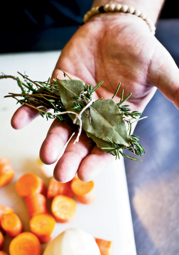 To create a bouquet garni for his vegetable soup, Perig ties together rosemary and thyme sprigs and a bay leaf.