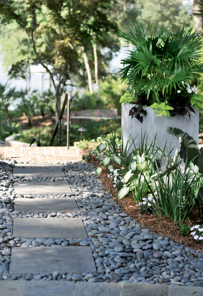 A Stone's Throw: Mexican river rocks add texture and function (covering spots where sod suffered from too much shade) along a path toward the river and boathouse.