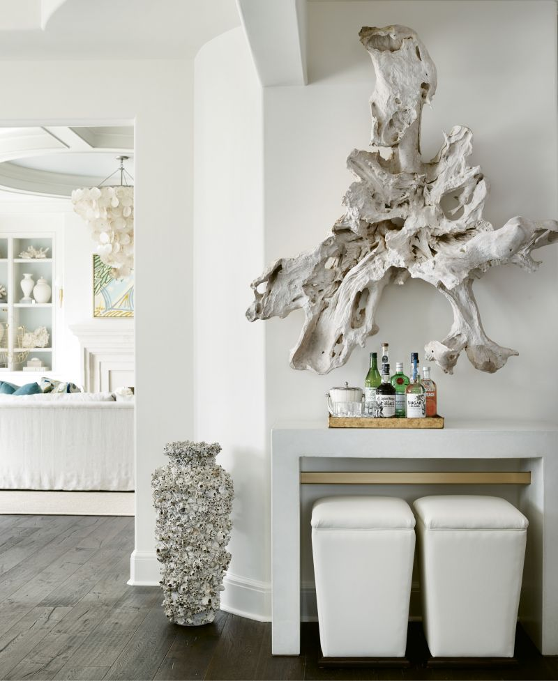 """Though the decor isn't overwhelmingly """"beachy,"""" there are nods to the coastal setting, like the piece of driftwood from Bali hung over a Bradley USA concrete console table and a capiz shell chandelier by Oly."""