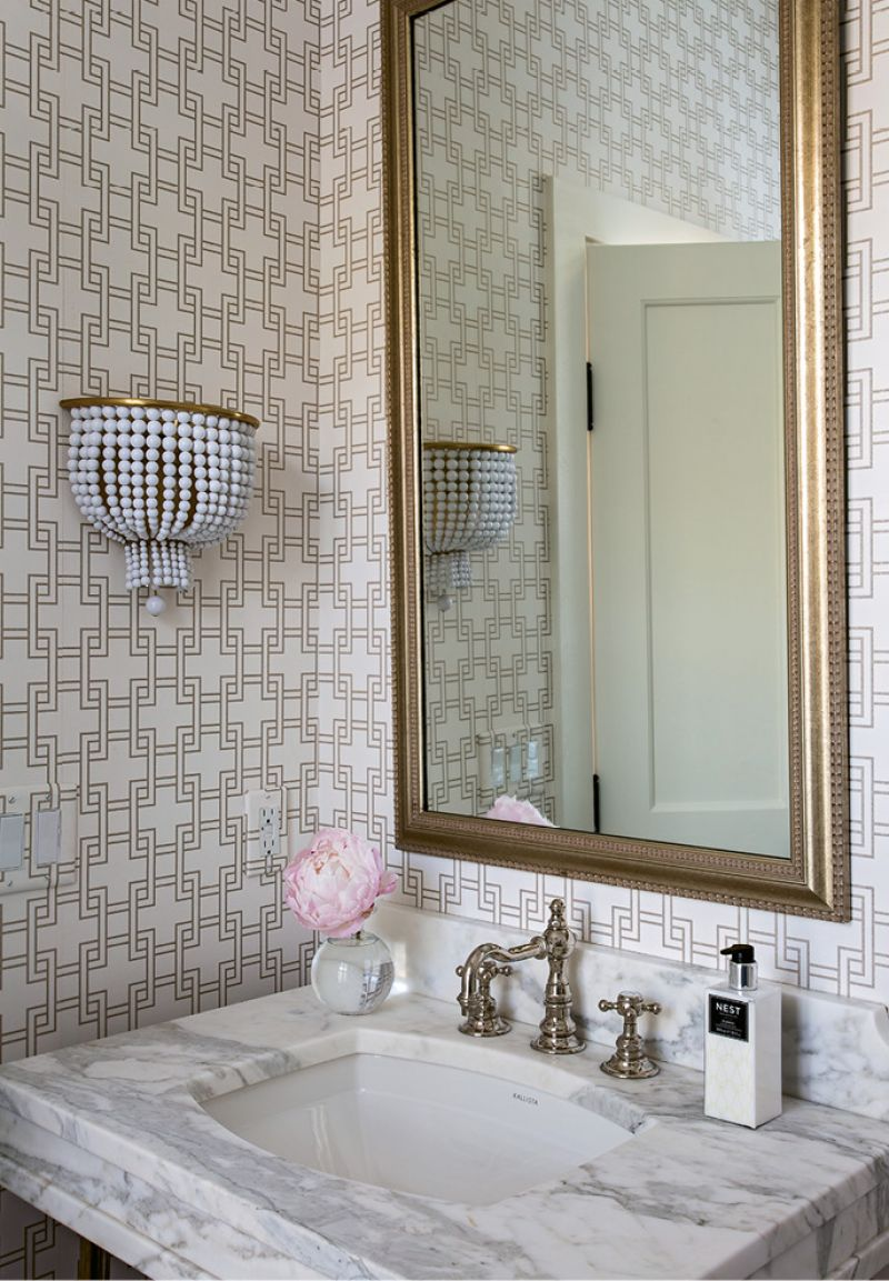 Elebash dressed up the powder room with geometric wallpaper from Romo and a beaded sconce from Circa Lighting.