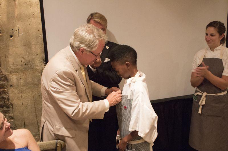 Louis Yuhasz and DaVee Harned watch as Mayor Tecklenburg awards Jaylen Jones for his hard work with Louie's Kids.