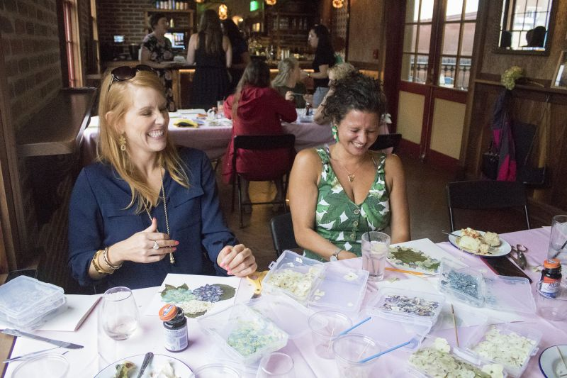 Meredith Siemens and Katie Strumpf share a laugh as they craft their designs.