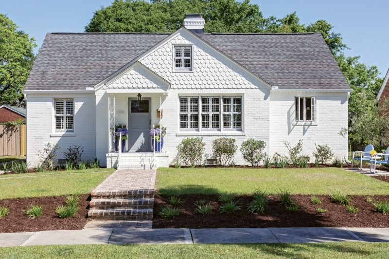 "FRESH FACED: To camouflage brick patchwork and better blend the scallop detailing with the rest of the façade, homeowner Rachel Levkowicz had the exterior coated in Benjamin Moore's ""White Dove,"" using Sherwin Williams' ""African Gray"" as an accent hue. Other Side of the River constructed the property's new walkway. ""It's one of my favorite things I added to the house,"" says Rachel."