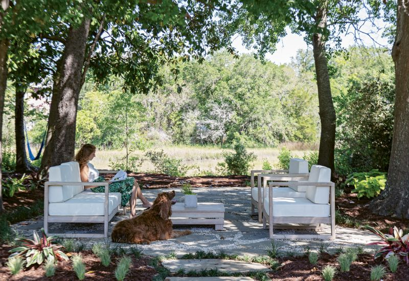 Out back, a lounge set from World Market offers marsh-side seating beneath a canopy of established trees.