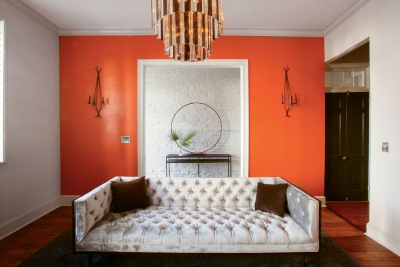 """A bold accent wall In Benjamin Moore's """"Fire Dance"""" enlivens the living room ."""